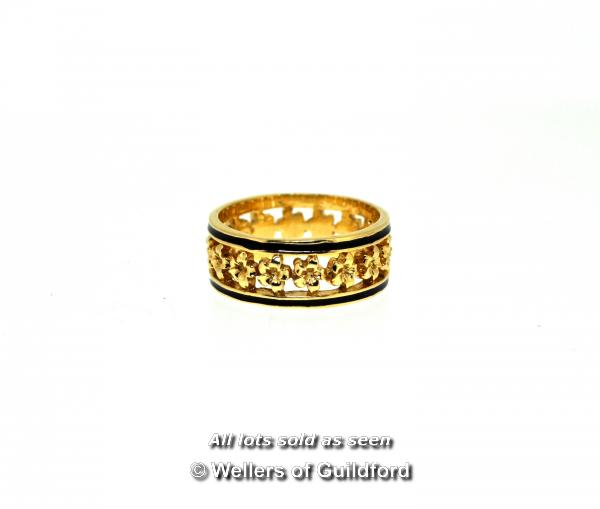 Ornate band ring, openwork band with a flower design and black enamel edges, in yellow metal stamped