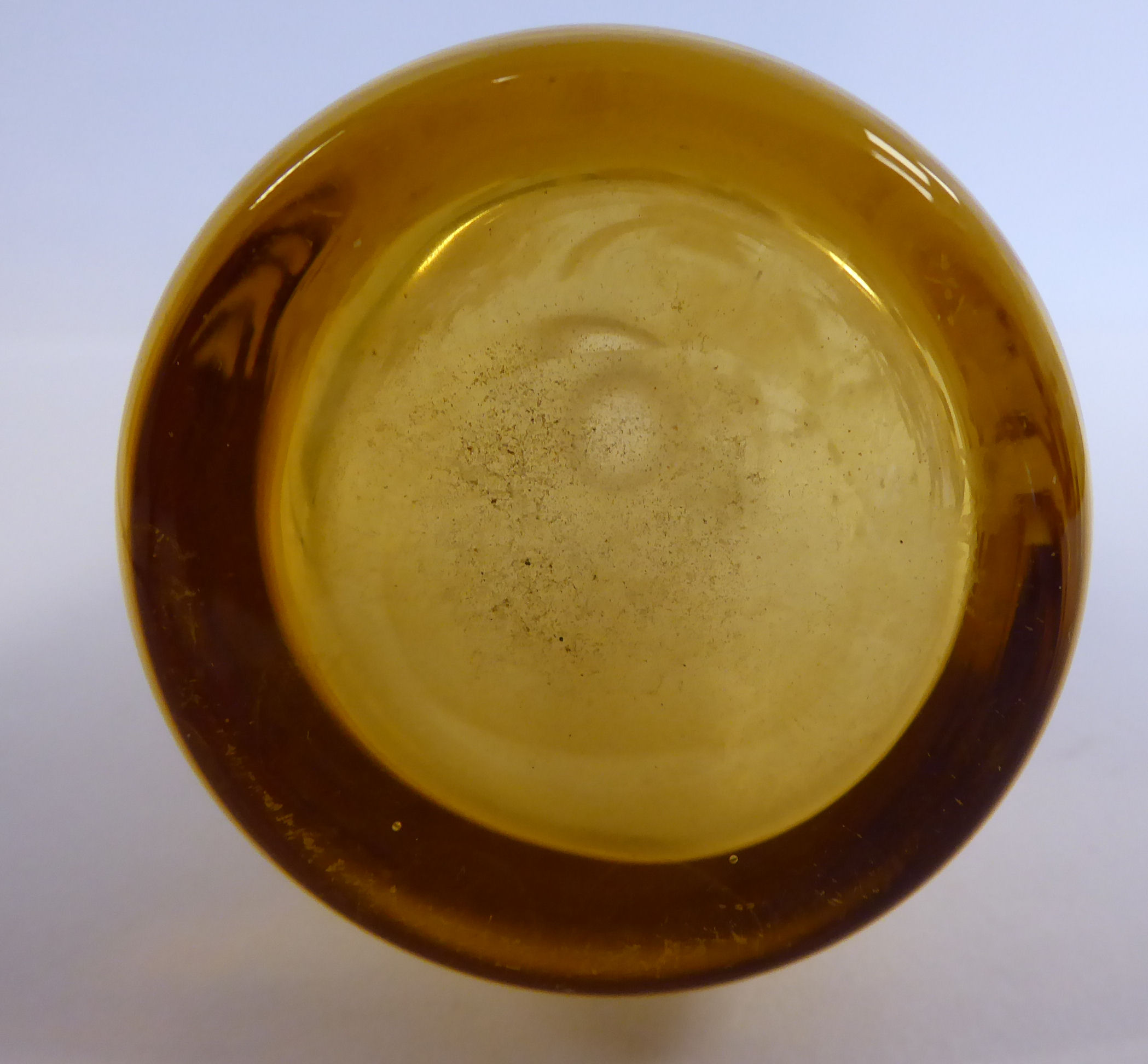 Lot 22 - In the manner of Mary Gregory - a tinted amber coloured glass jug of tapered form with a drawn loop