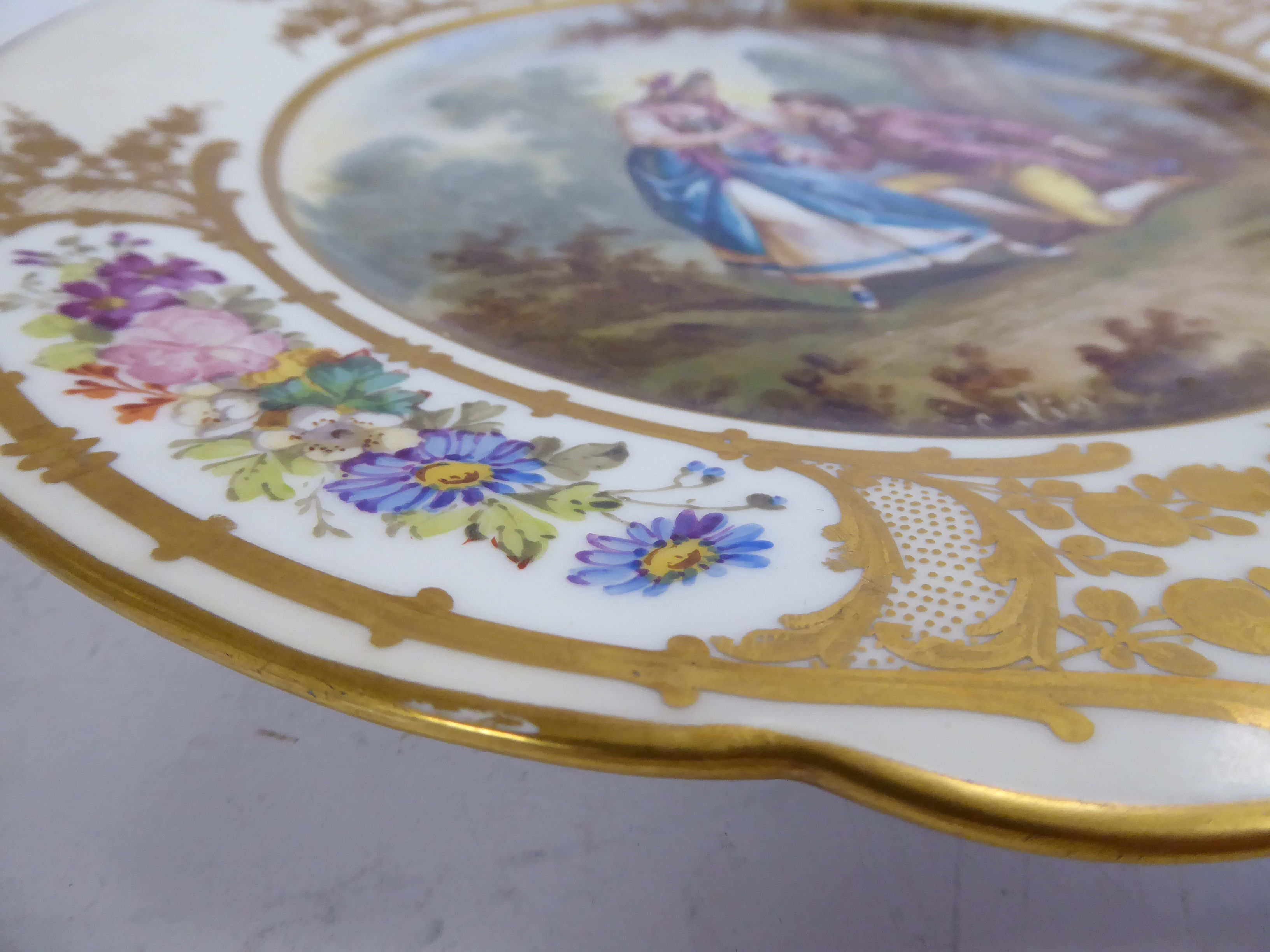 Lot 6 - A mid 19thC Sevres porcelain wavy edged plate, featuring a romantic scene,