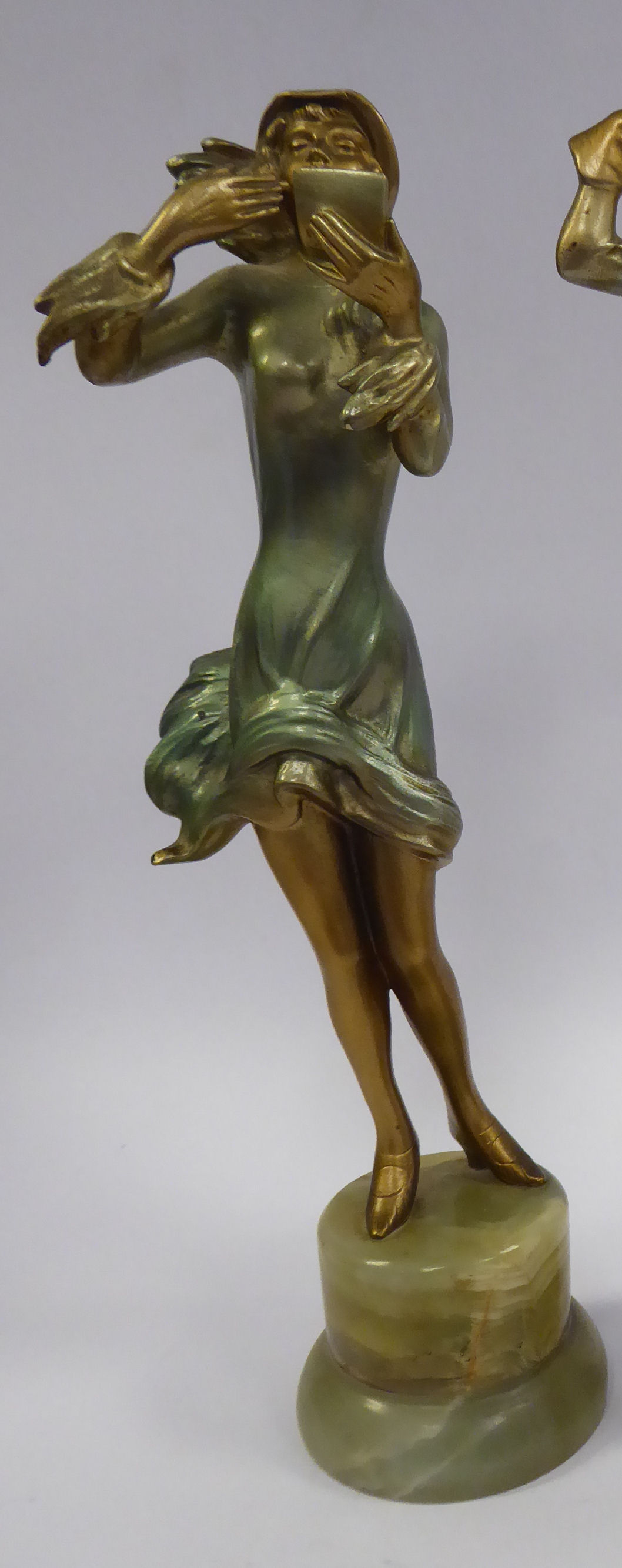 Lot 56 - A late 1920s/early 1930s painted cold cast figure, a fashionable young woman, wearing a bonnet,