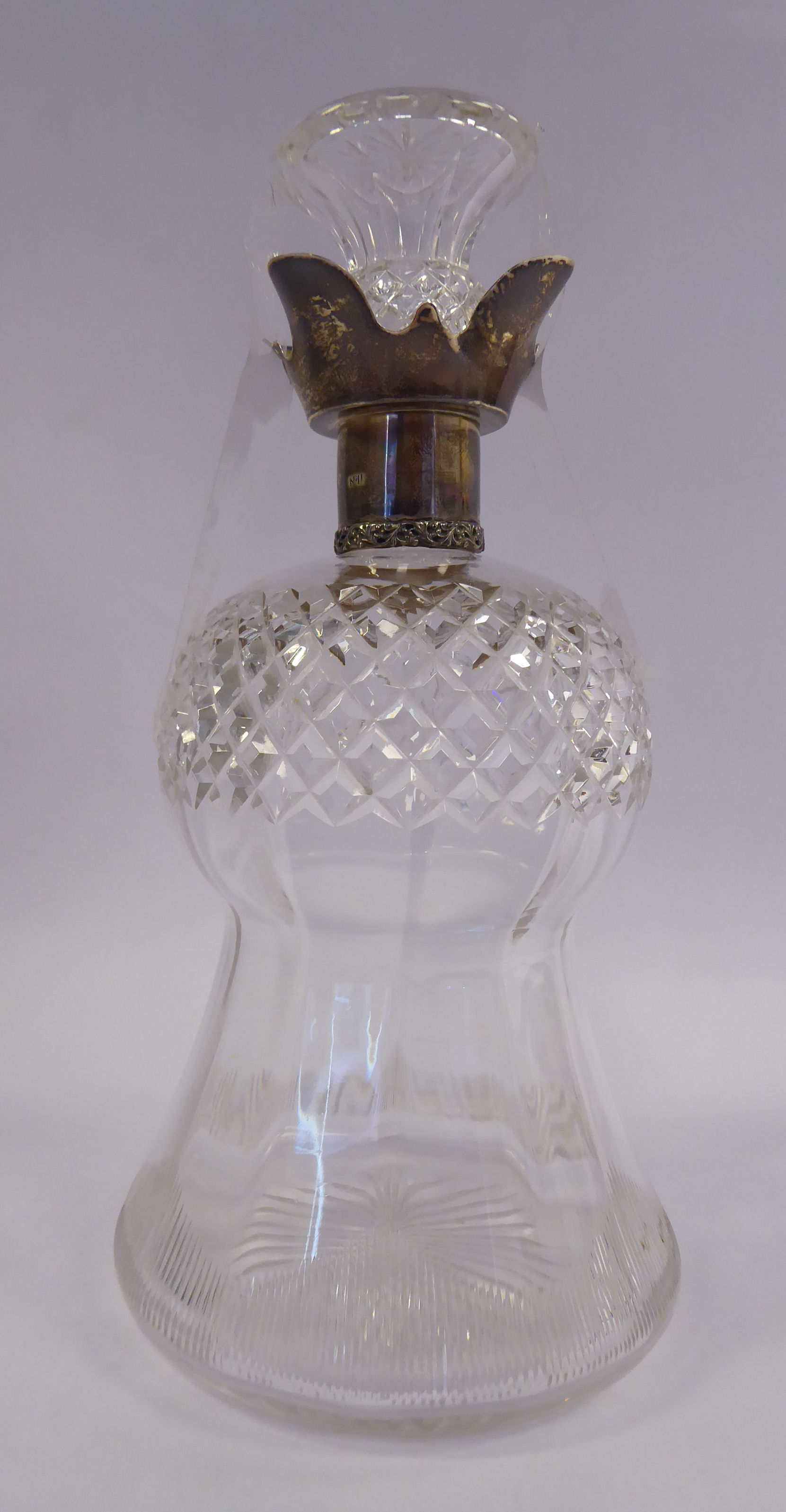 Lot 20 - An Edwardian thistle design glass decanter with slice and diamond cut ornament and an applied,