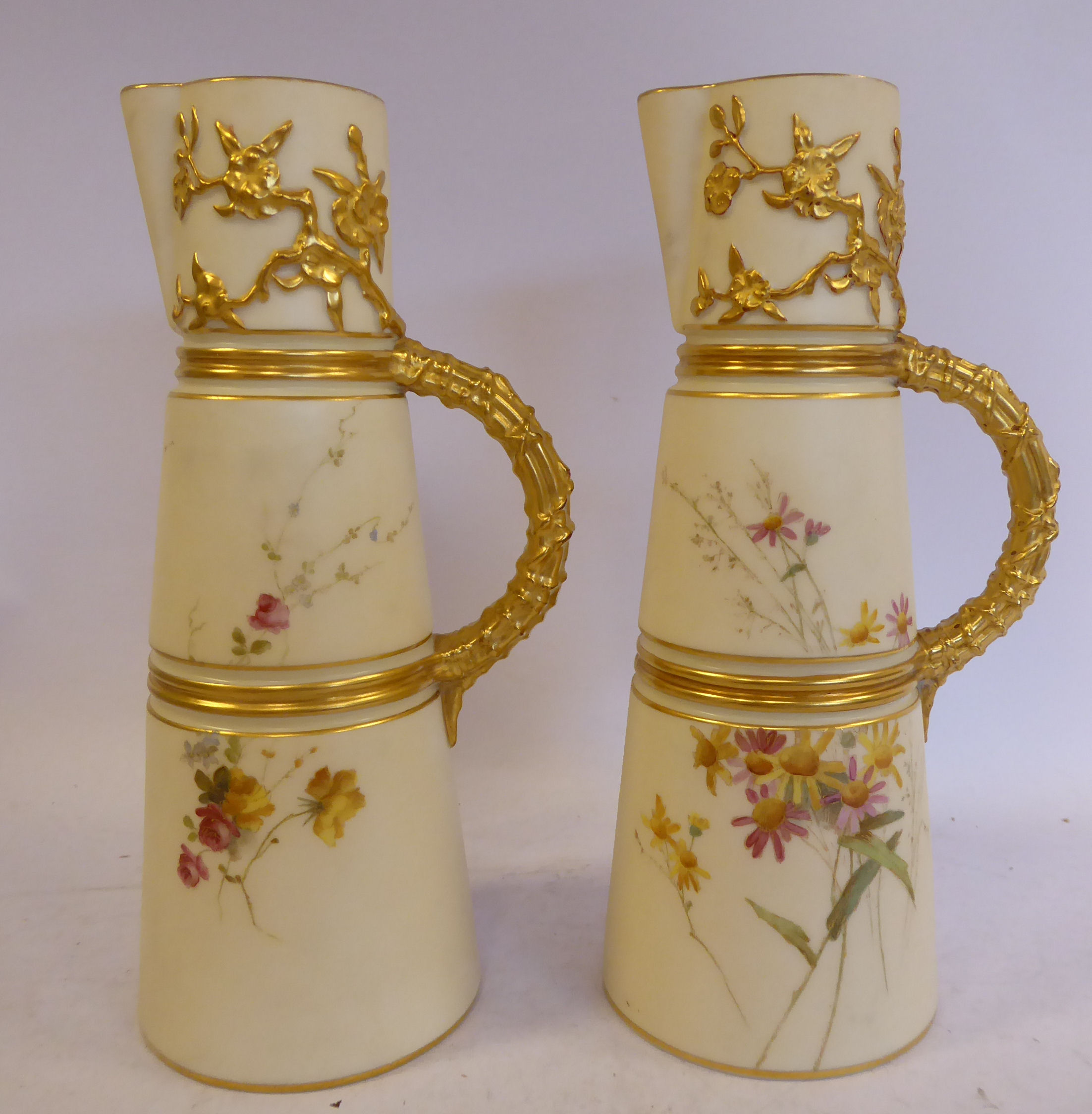 Lot 3 - A pair of Royal Worcester blush ivory glazed china jugs of banded,