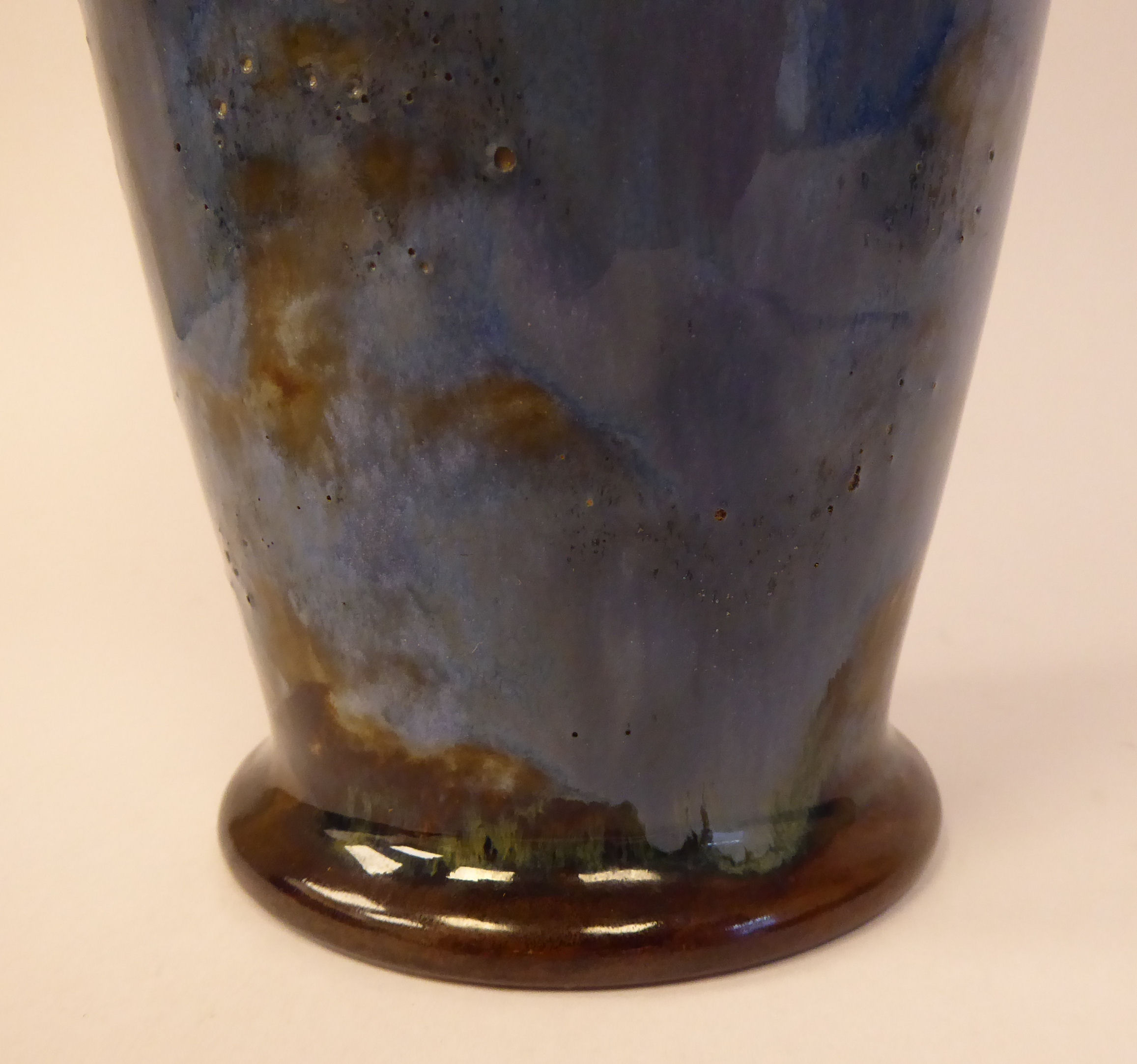 Lot 2 - An early 20thC Royal Doulton sponged blue, green and white glazed stoneware vase of slender,