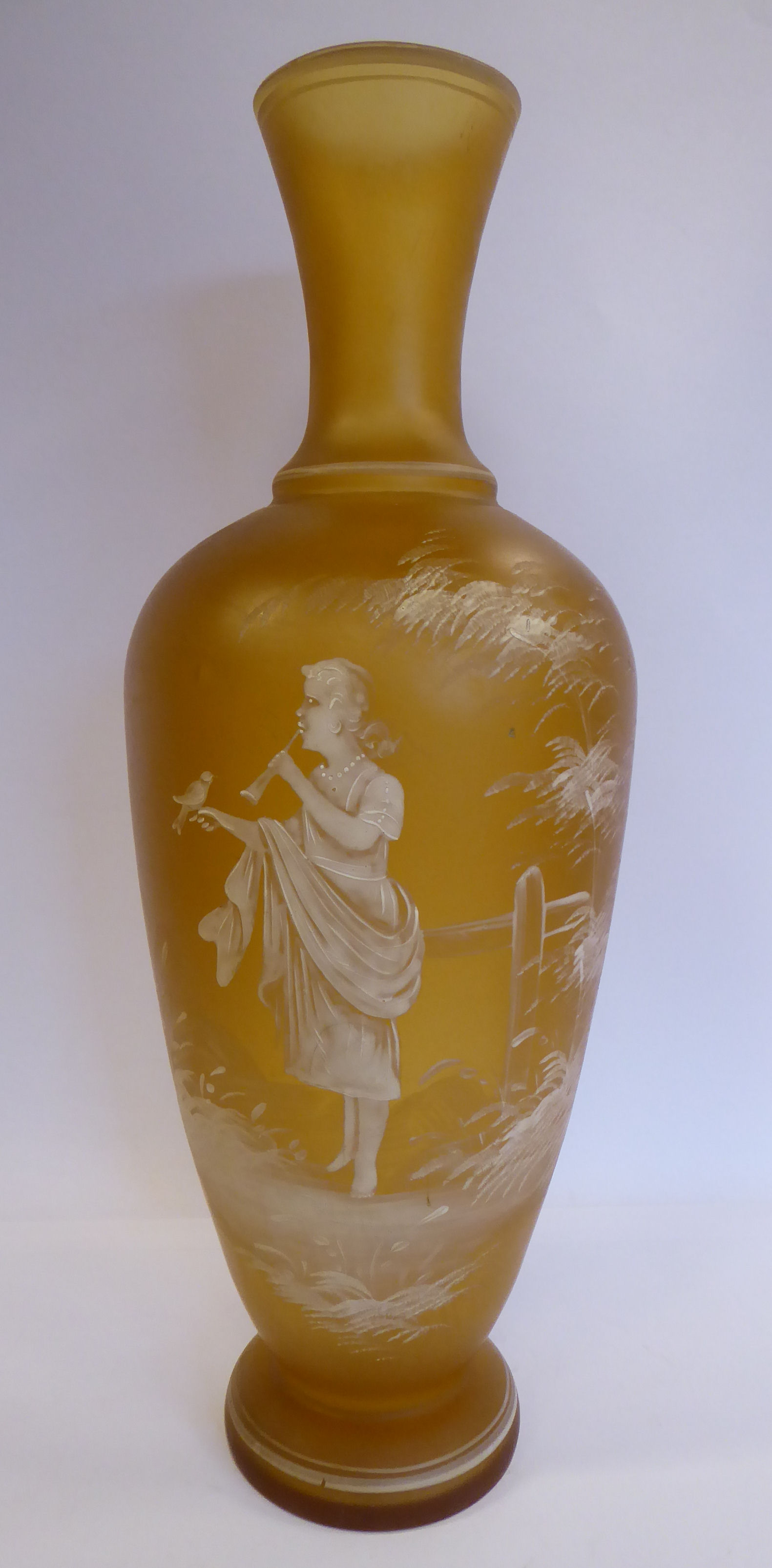 Lot 27 - In the manner of Mary Gregory - a semi-opaque amber coloured glass vase of baluster form with a