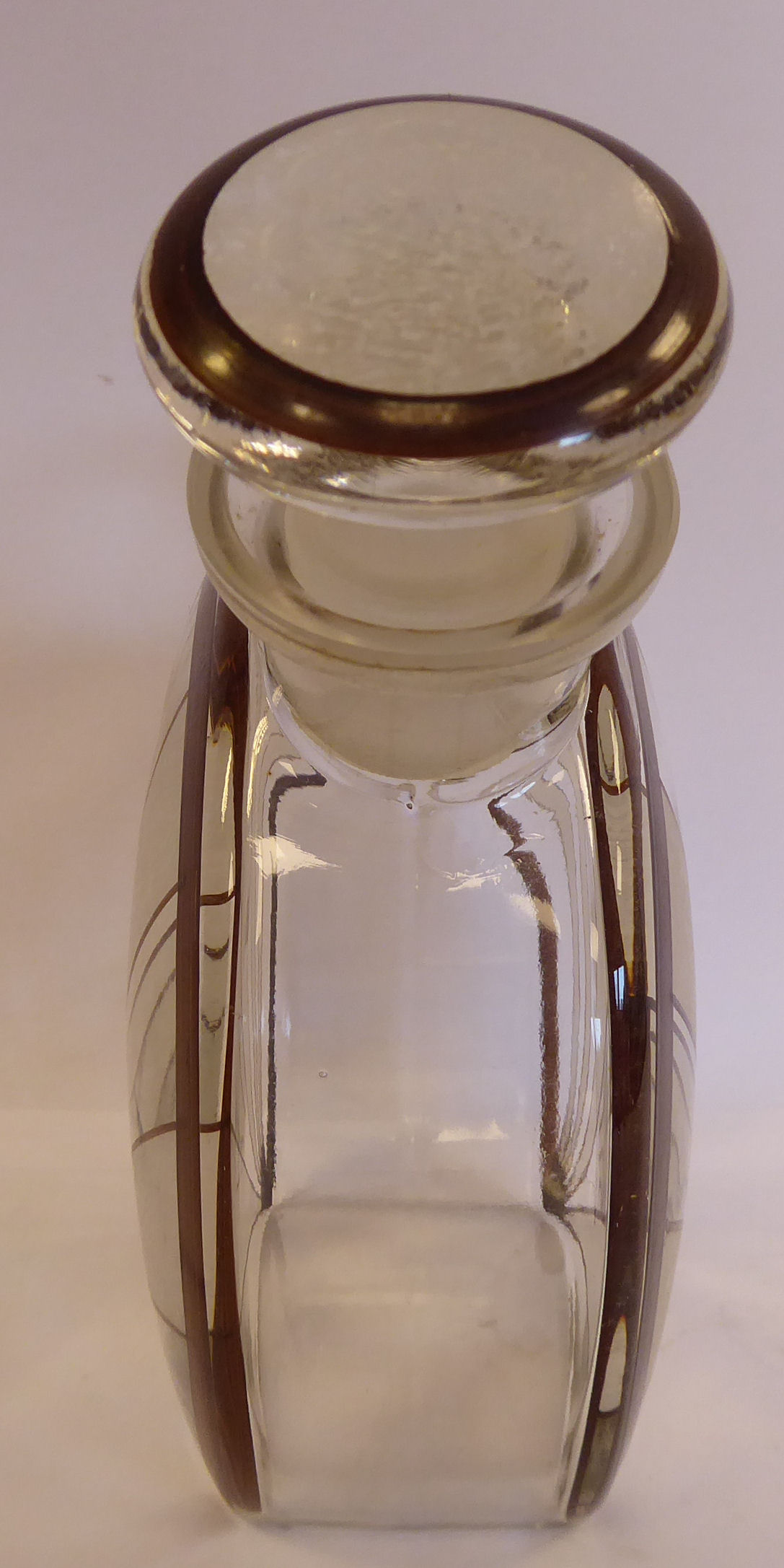 Lot 17 - An Art Deco clear glass liqueur decanter of moonflask design with a drawn loop handle,