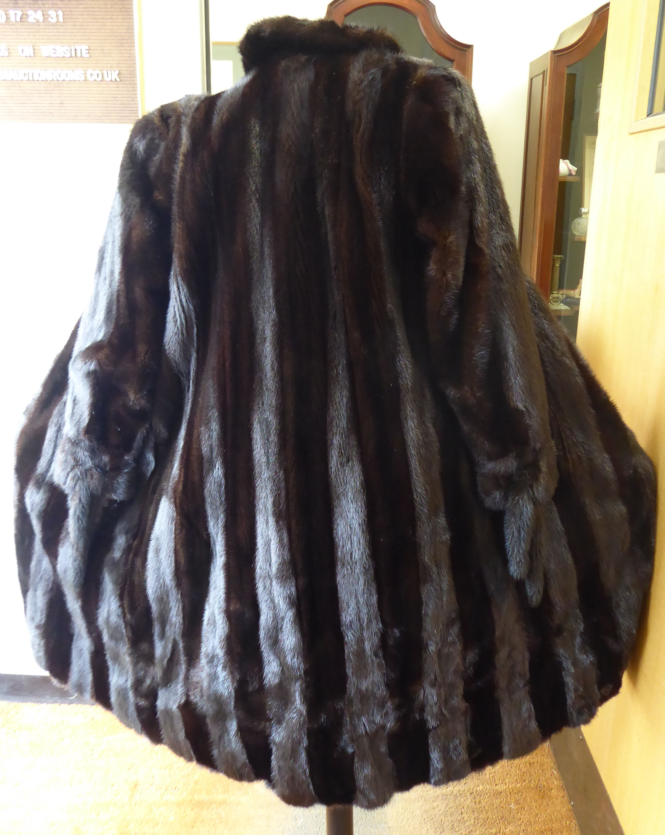 Lot 31 - A black mink knee length fur coat with a collar,