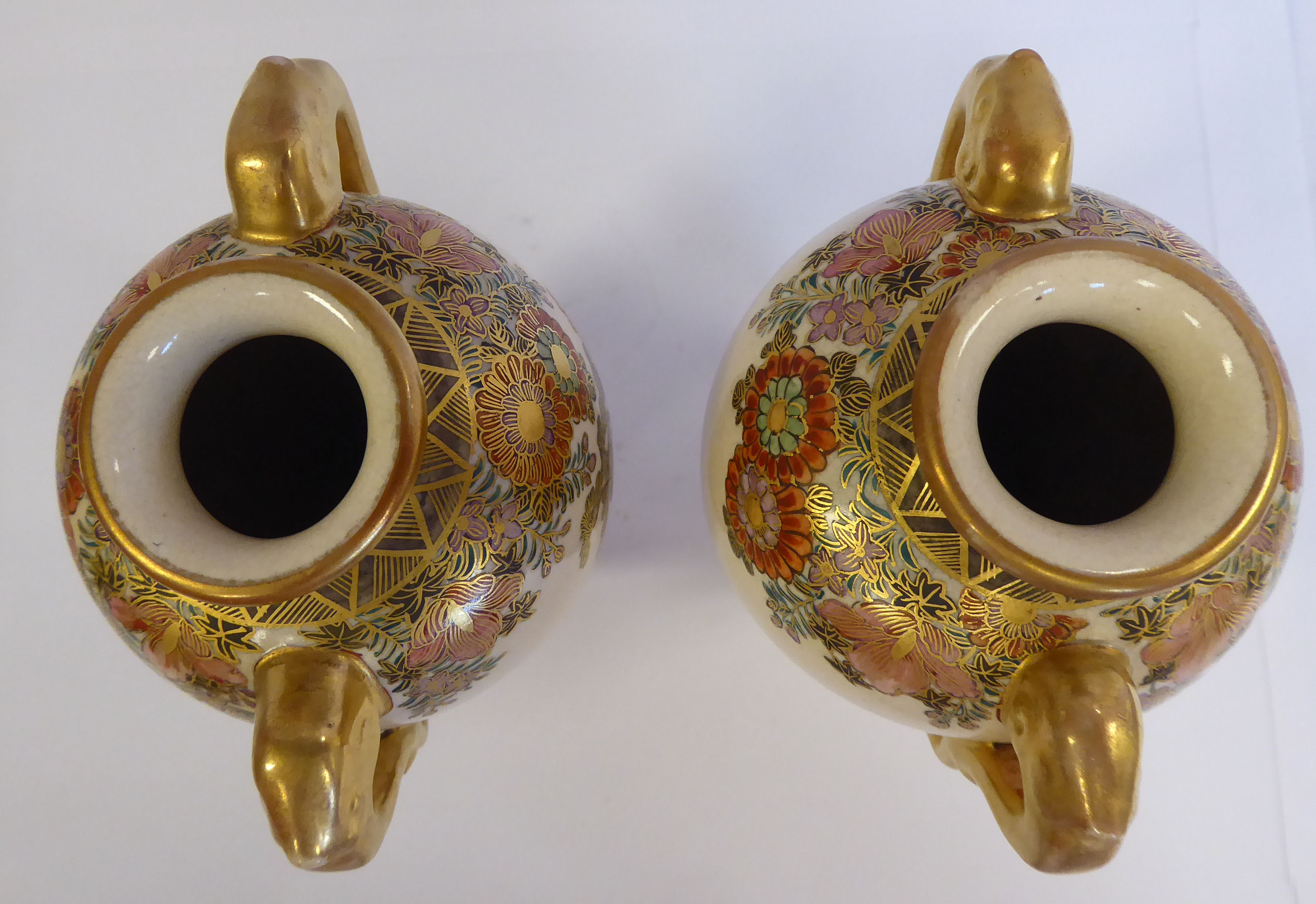 Lot 11 - A pair of 20thC Satsuma gilded earthenware baluster shaped vases with opposing, moulded handles,