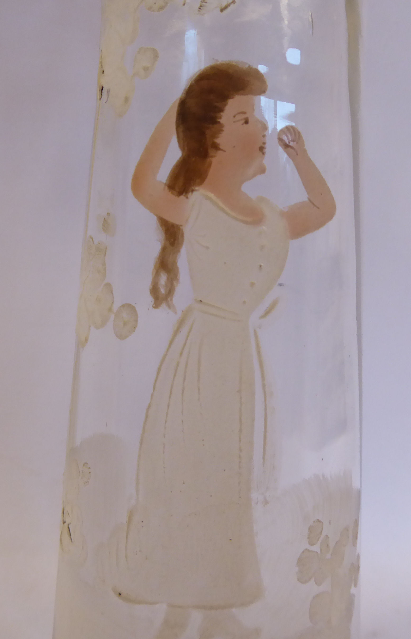 Lot 24 - In the manner of Mary Gregory - a clear glass vase of tapered cylindrical form with a flared,
