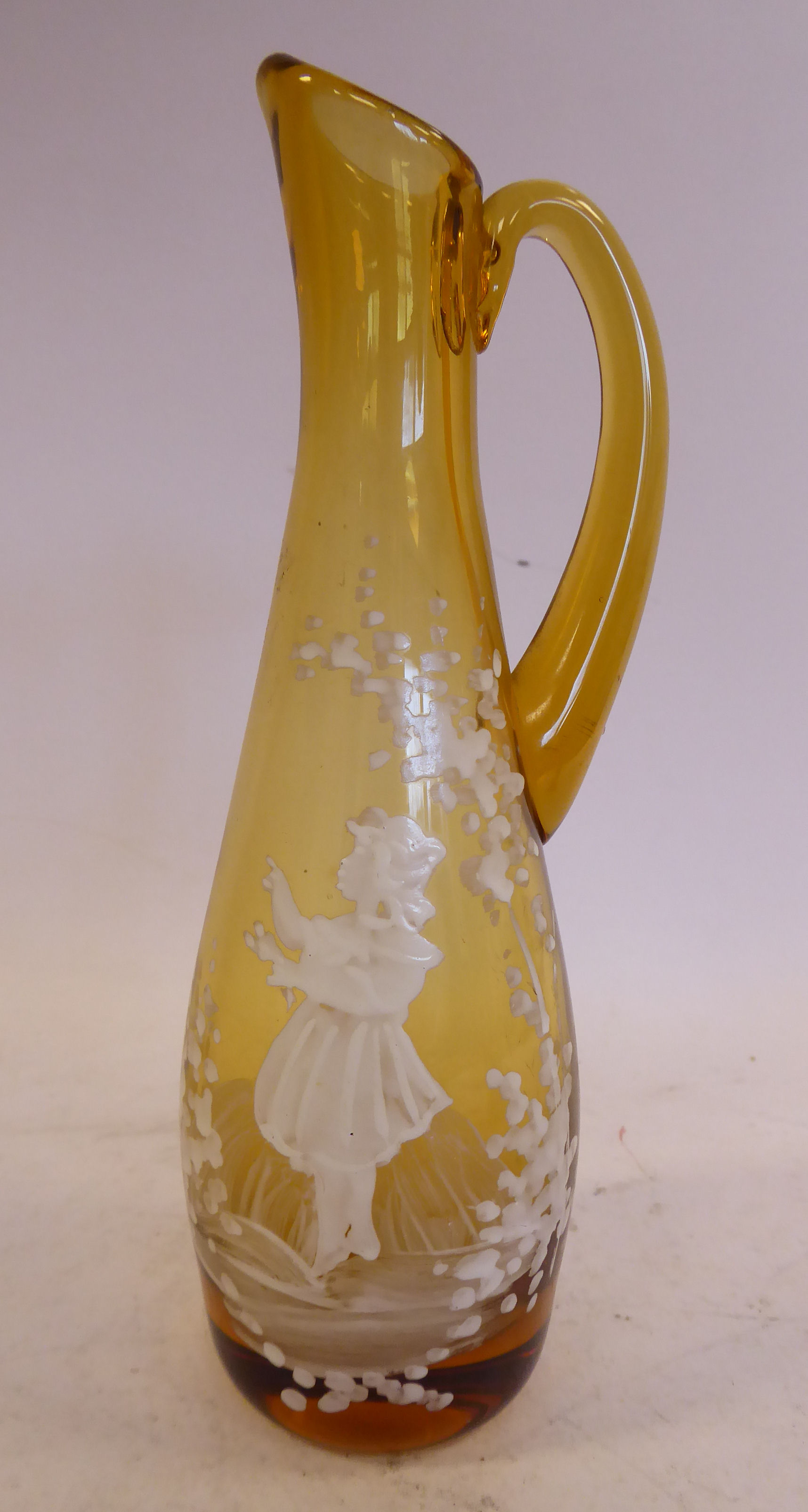 Lot 23 - In manner of Mary Gregory - a tined amber coloured glass jug of tapered form with a drawn loop