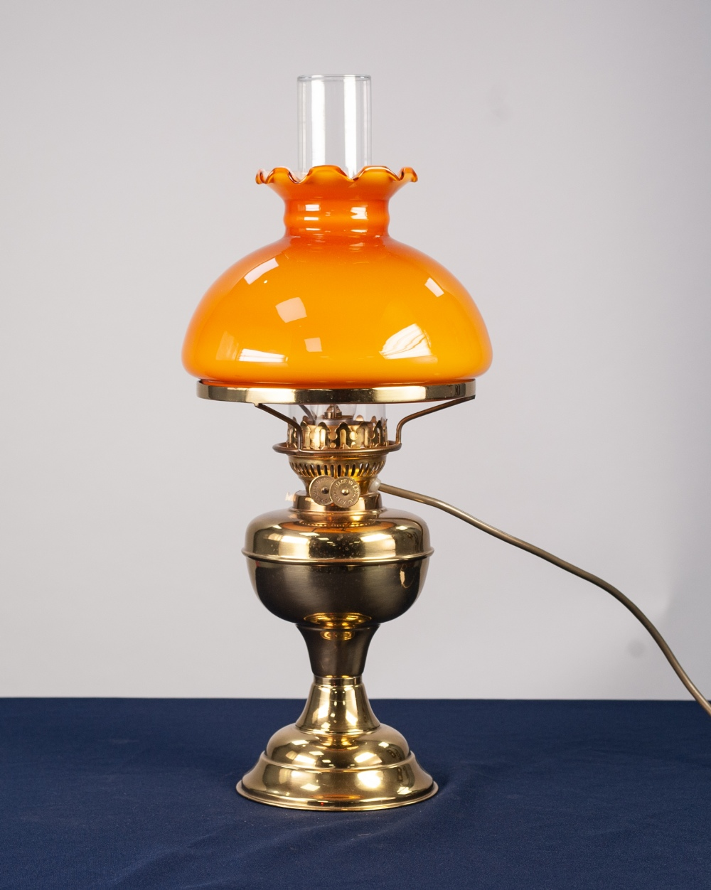 Lot 28 - AN ADAPTED OIL LAMP WITH ORANGE GLASS GLOBE AND CLEAR GLASS FUNNEL