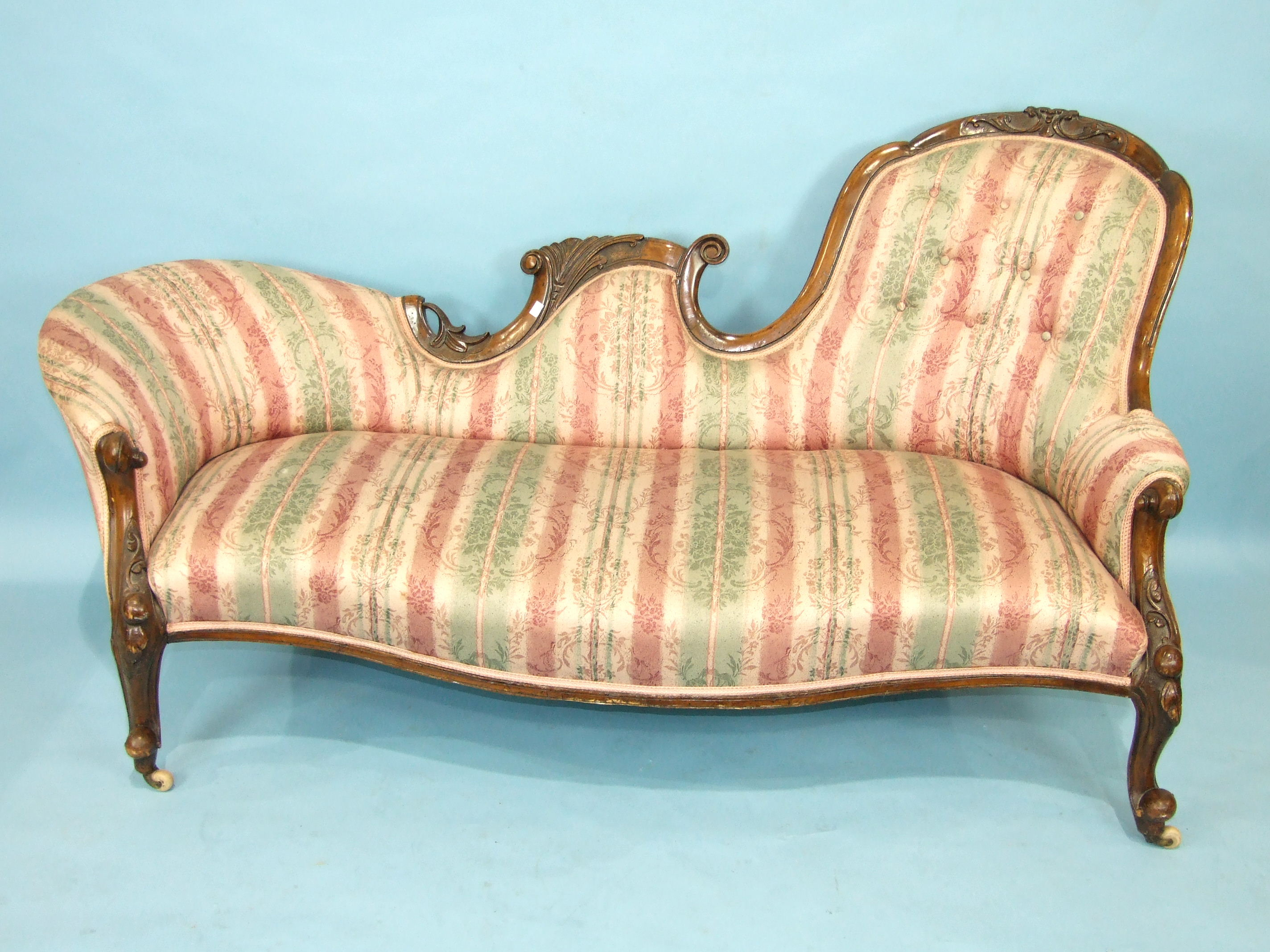 A Victorian walnut settee, the carved frame and cabriole legs with upholstered shaped back and