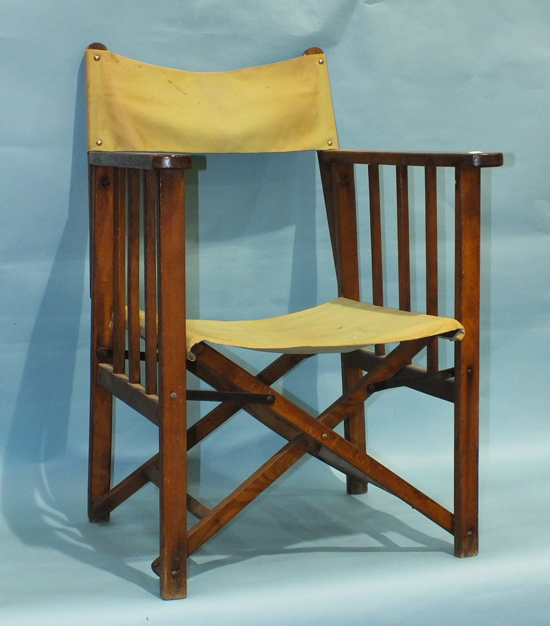 A vintage stained wood folding deck chair/pilot's chair with canvas back and seat. (Belonged to a