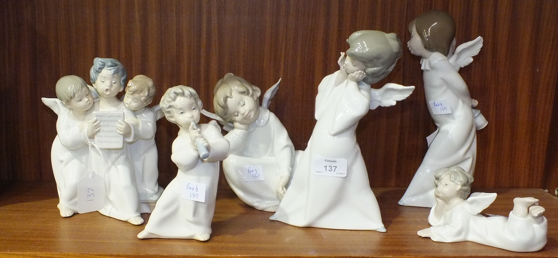 Lot 137 - Six Lladro angelic figures, one playing a pipe, a group of three choristers and four others, (6).