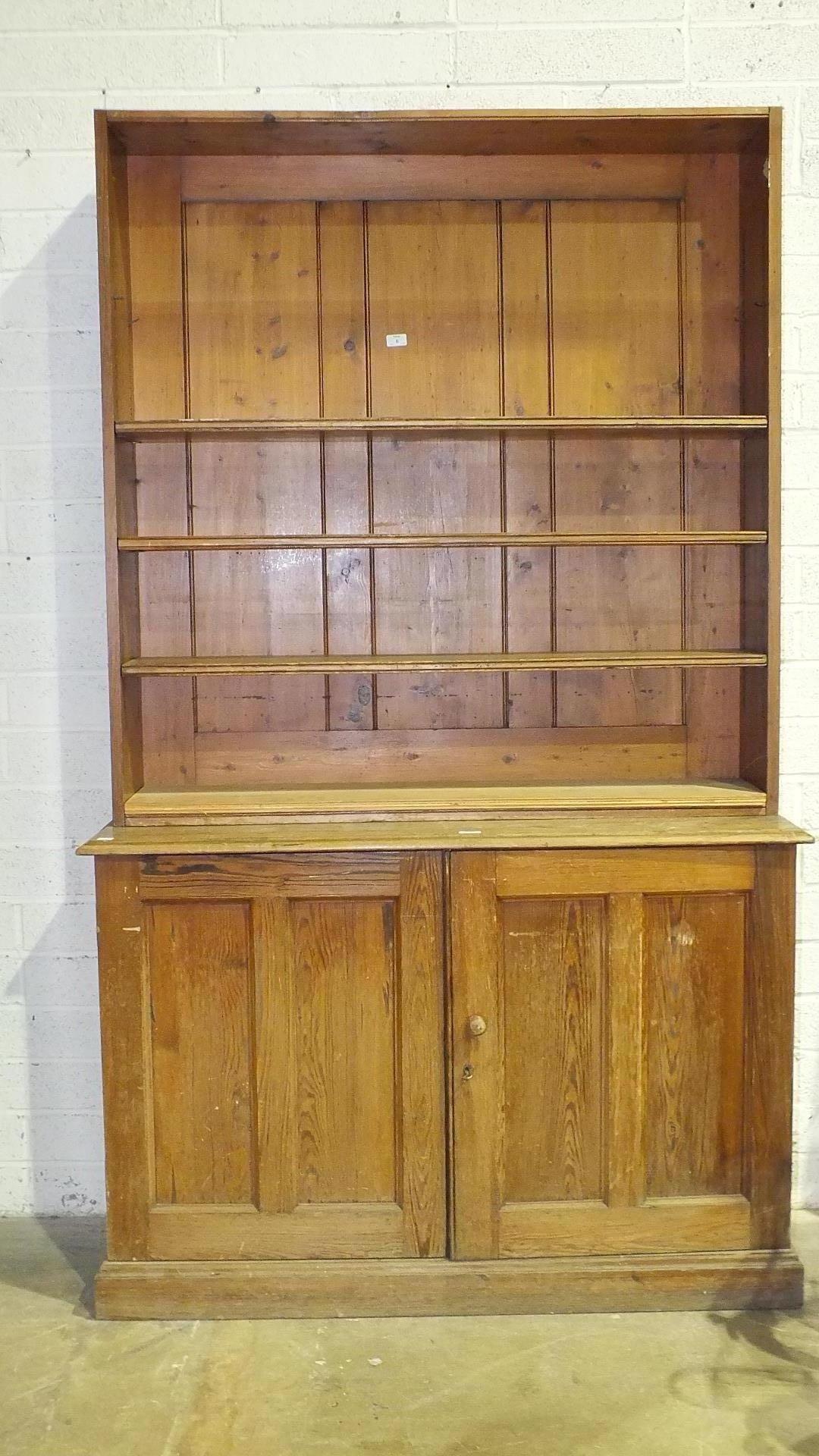 A pitch pine bookcase, the open shelves above a pair of panel doors, 127cm wide, 204cm high, (