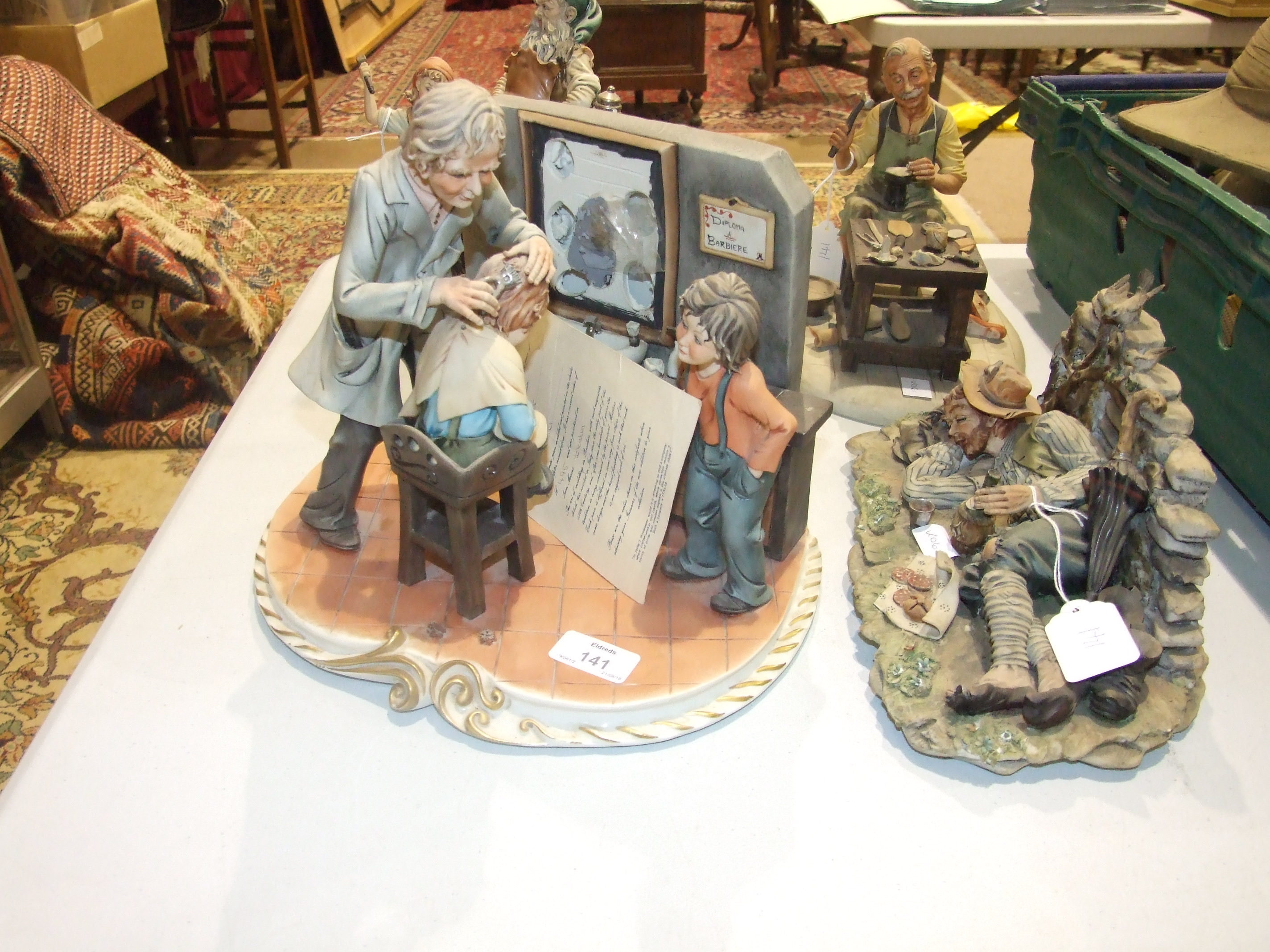 "A modern Capo di Monte figure group, ""The Barber"" by Corti, 22cm high, another, ""The Cobbler"" and"