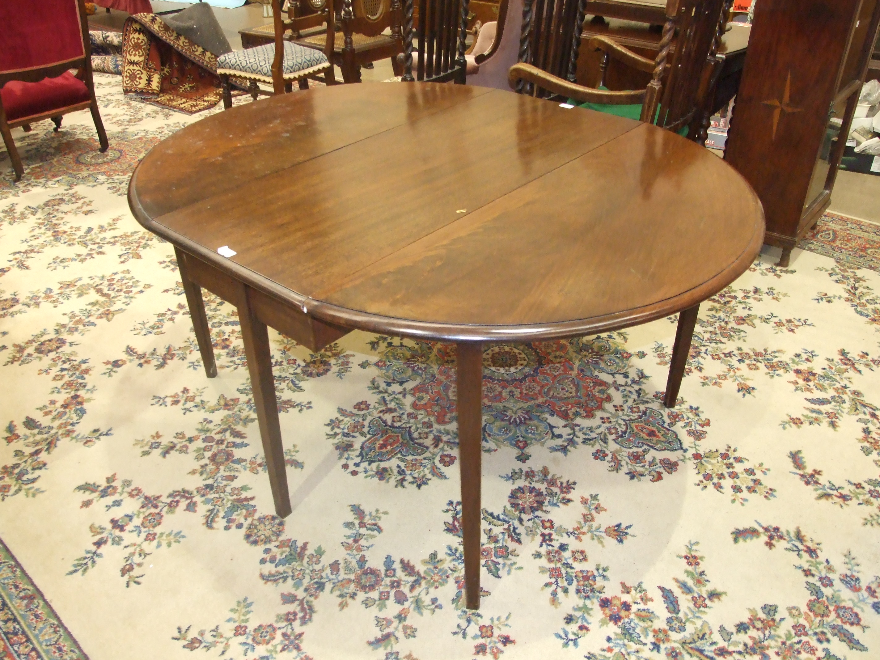A Georgian mahogany drop leaf dining table with two oval leaves on square tapered legs, 154 x