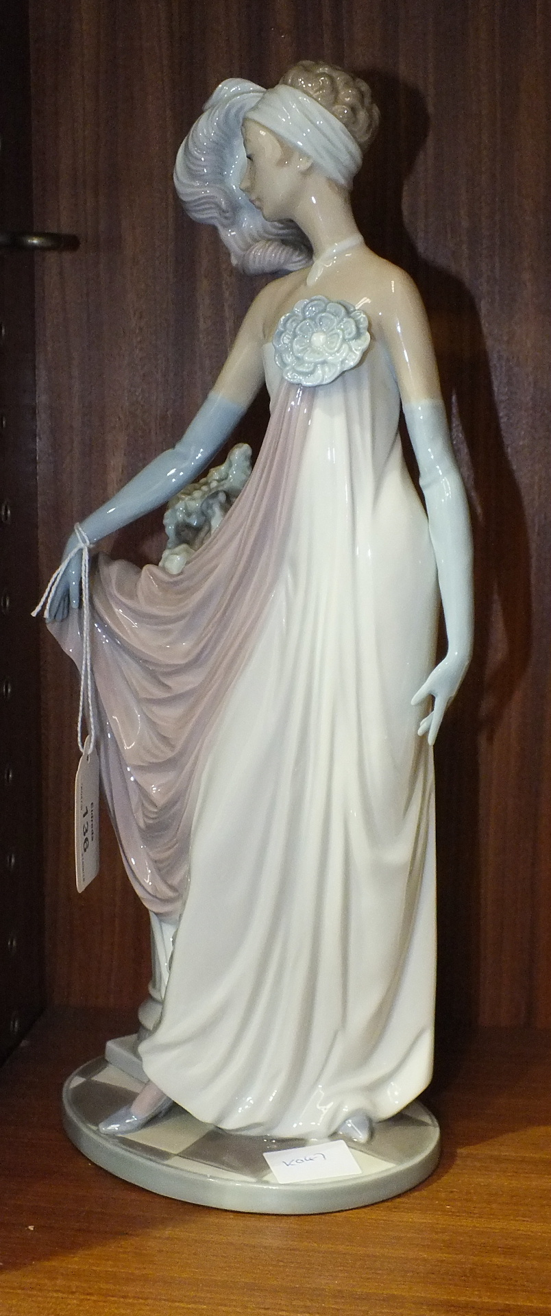 Lot 136 - A Lladro figure of a young woman with plumed head dress and evening gown standing by a pedestal of