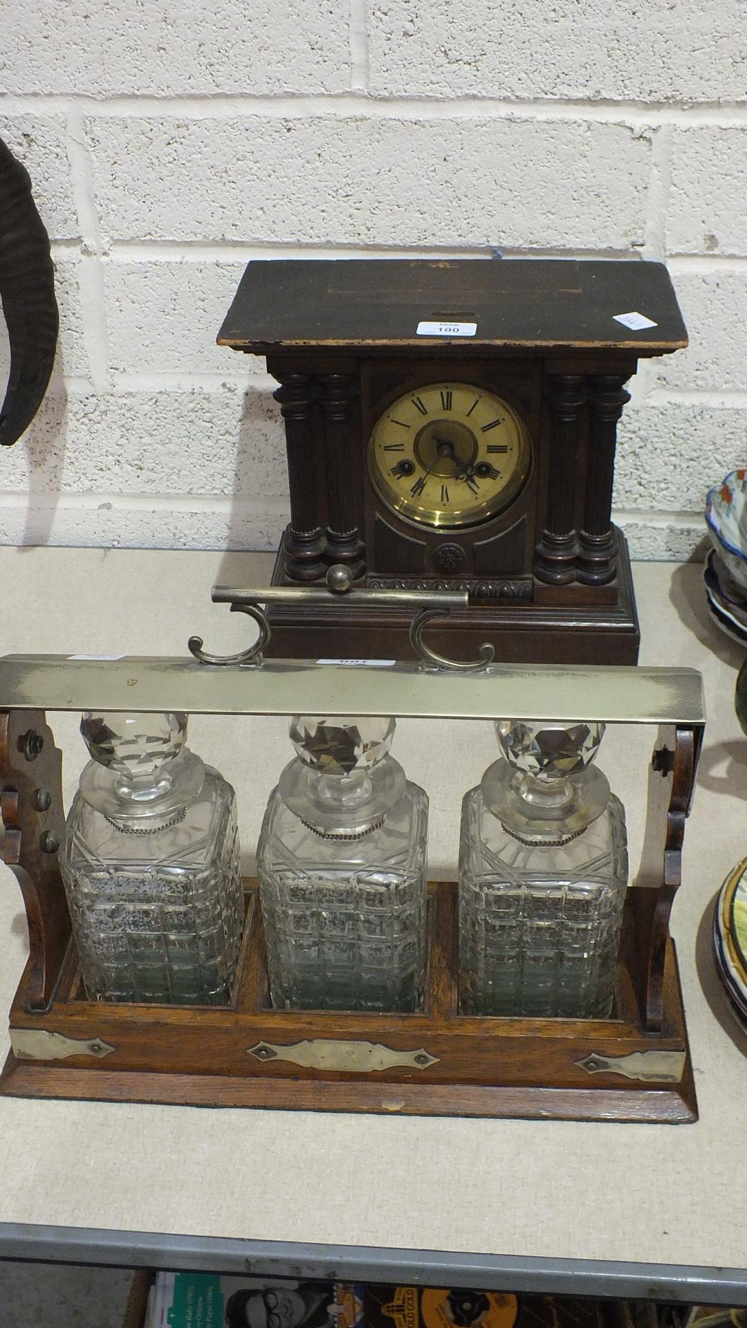 An oak Tantalus with plated mounts, containing three glass decanters, (a/f), 38cm wide, 30cm high