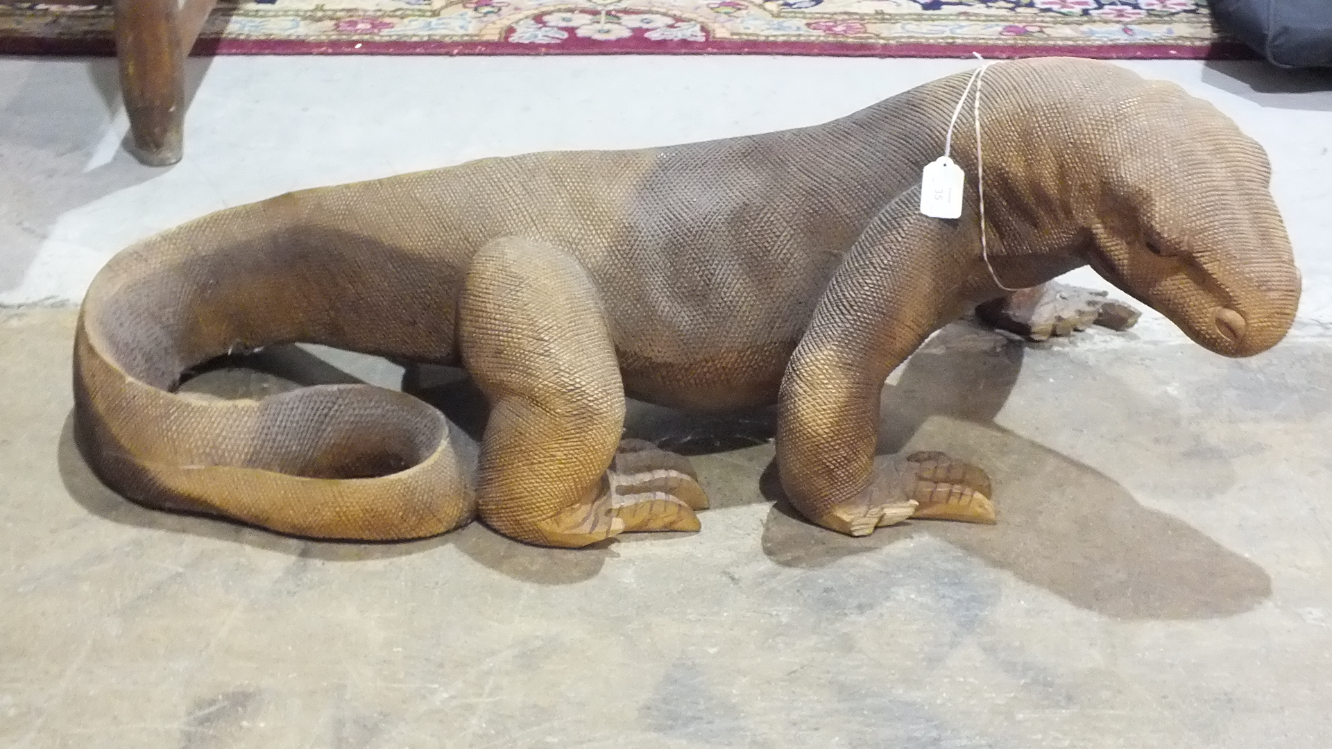 An Indonesian carved wood model of a Komodo dragon, 100cm long, 38cm high, (some losses to toes).