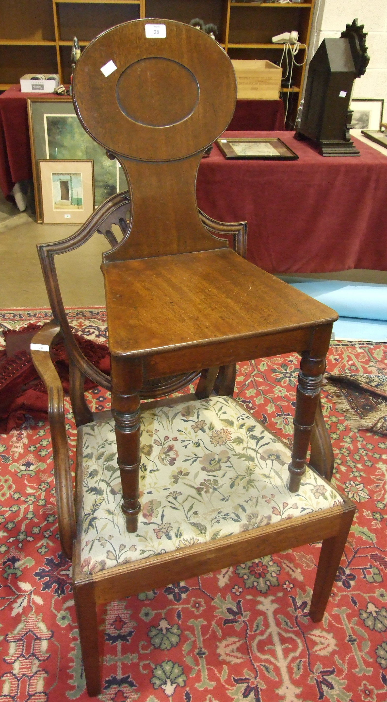 A Victorian mahogany hall chair, the solid back and seat on turned front legs and a Georgian