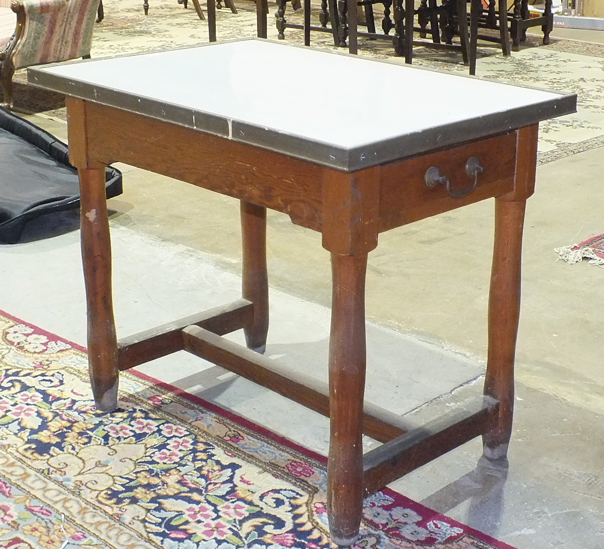 An enamelled top pine food preparation table, the rectangular top with brass edges above two end-