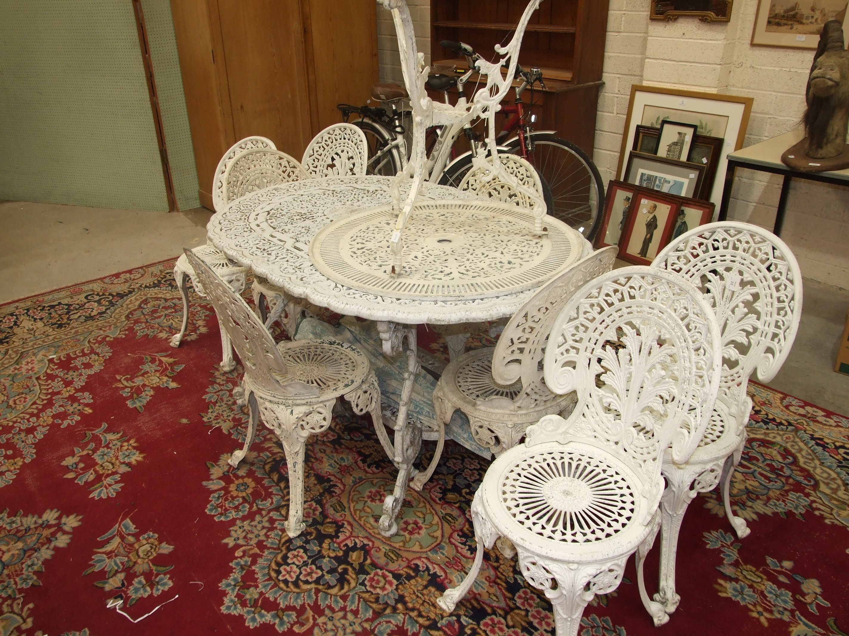 A painted metal garden-table of pierced foliate design, 140cm long, together with eight chairs and a