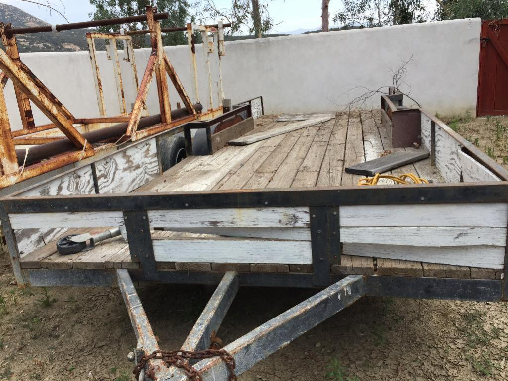 "Lot 109 - Trailer 2 axle 20ft. with tires and mud guard. Metal stake perimeter about 12"" high. Wood plank plat"