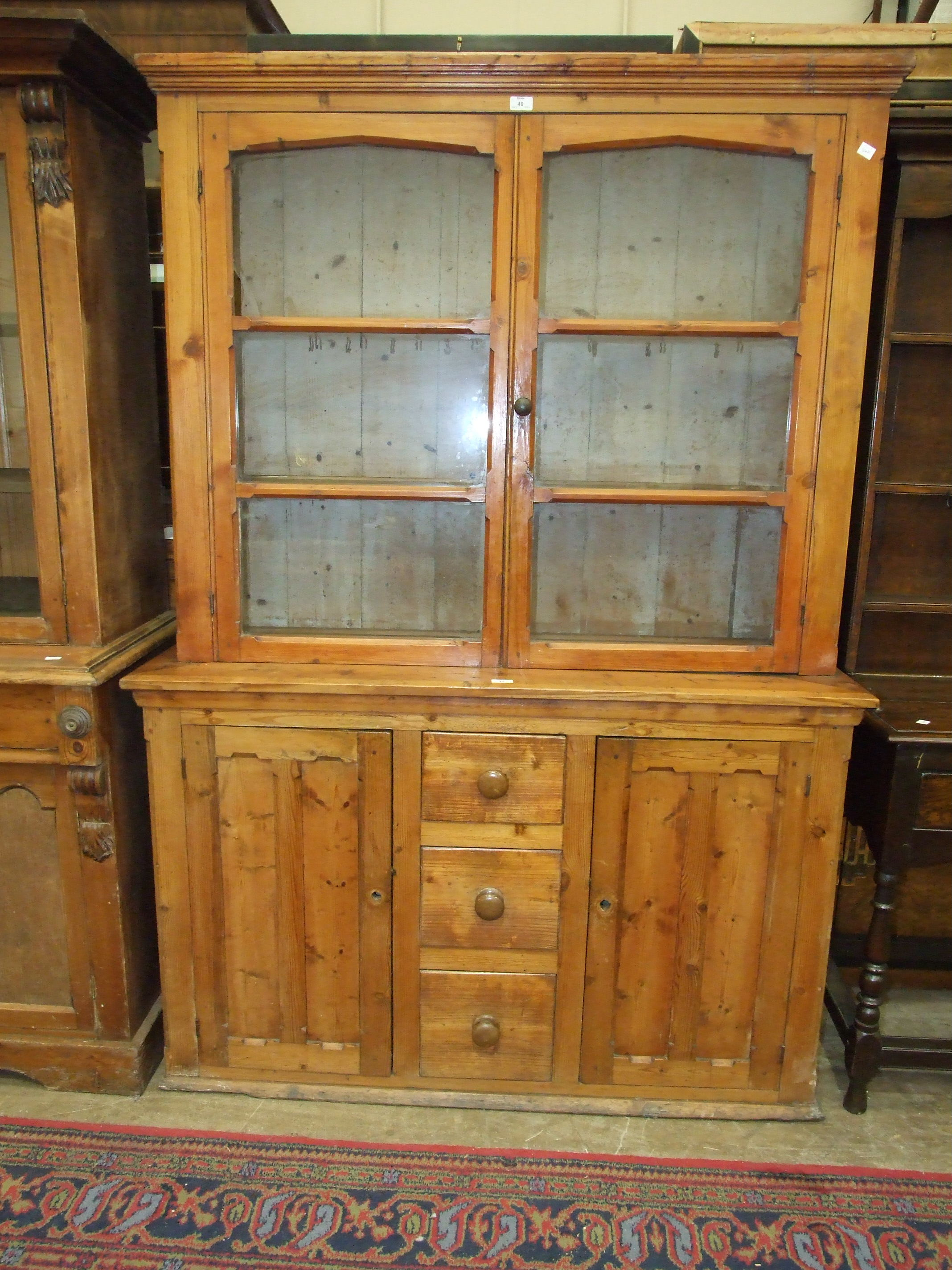 Lot 40 - A stained pine dresser, the shelved top fitted with a pair of glazed doors, above three small