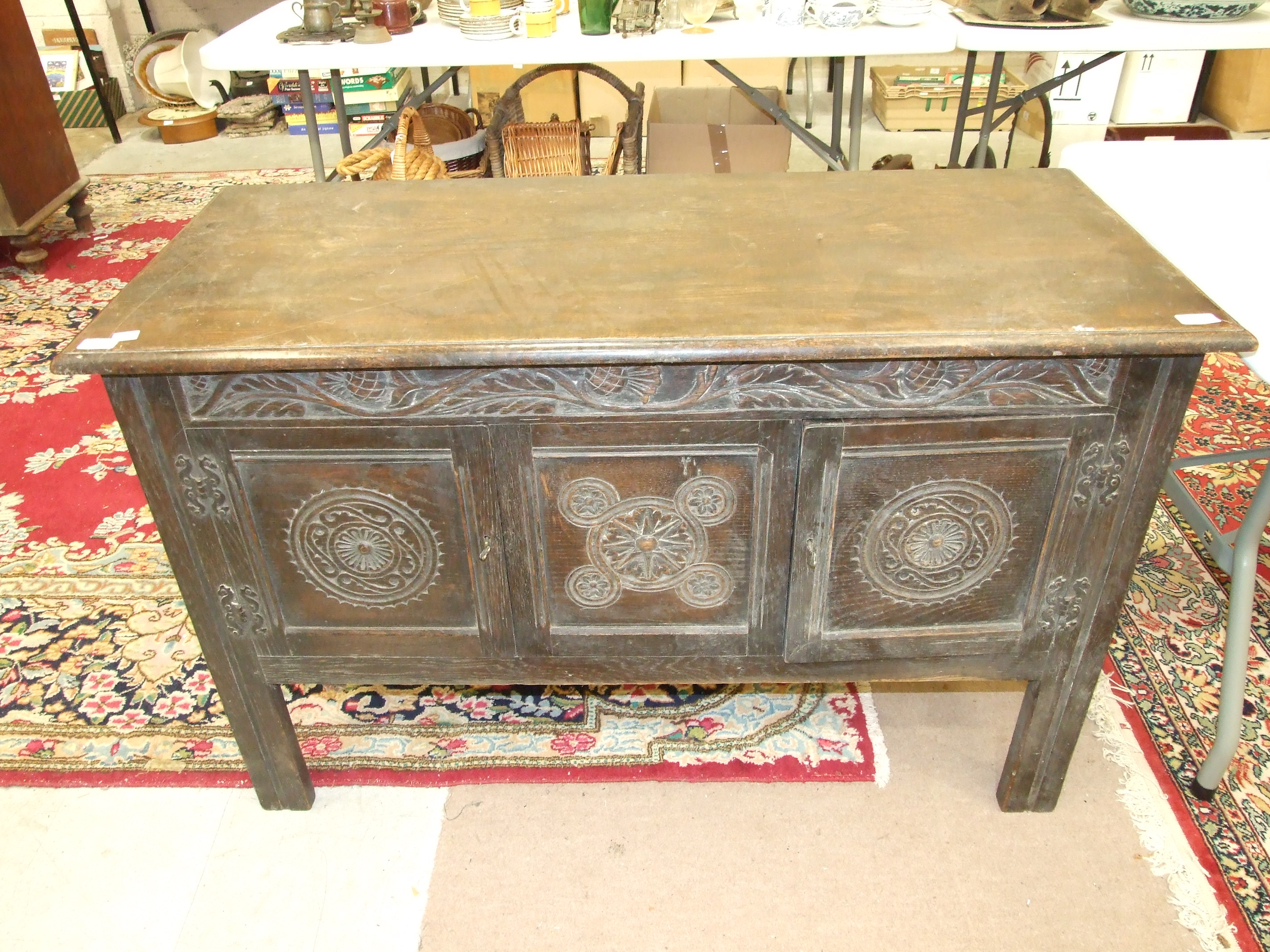 Lot 31 - An oak low sideboard, the rectangular top above a pair of carved panel doors, 120cm wide.