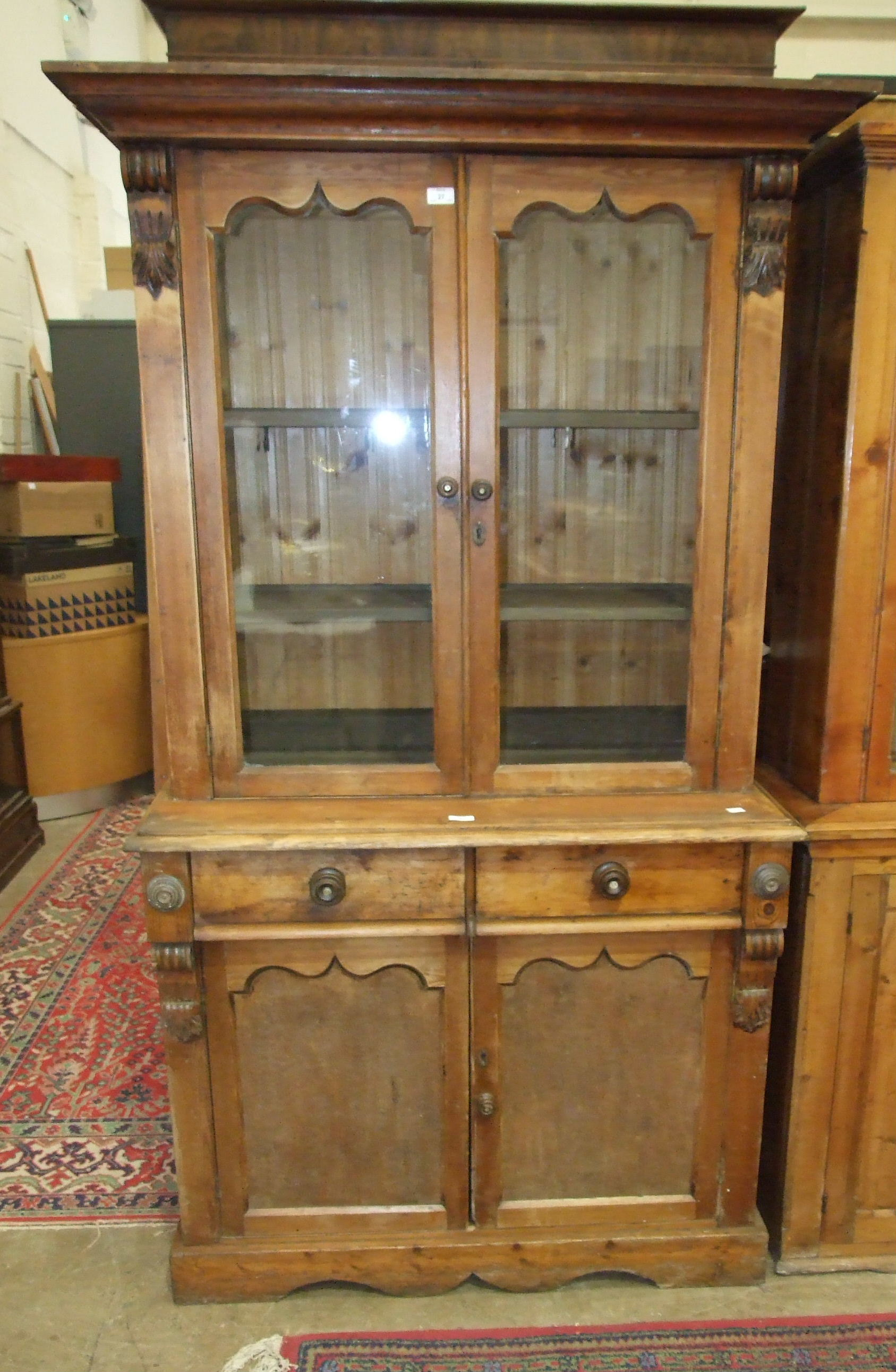 Lot 27 - A late-19th century stained pine bookcase, the top fitted with a pair of glazed doors above two