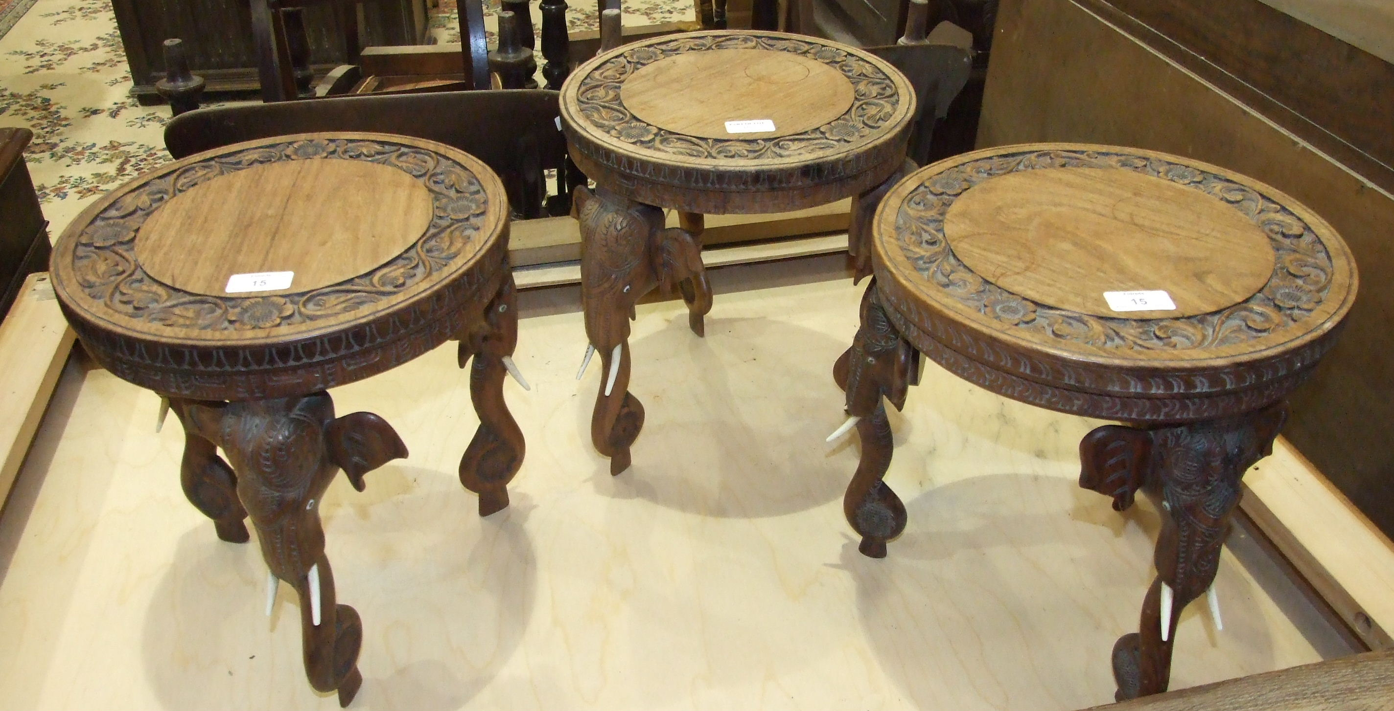 Lot 15 - Three carved hardwood occasional tables with carved elephant mask legs, (3).