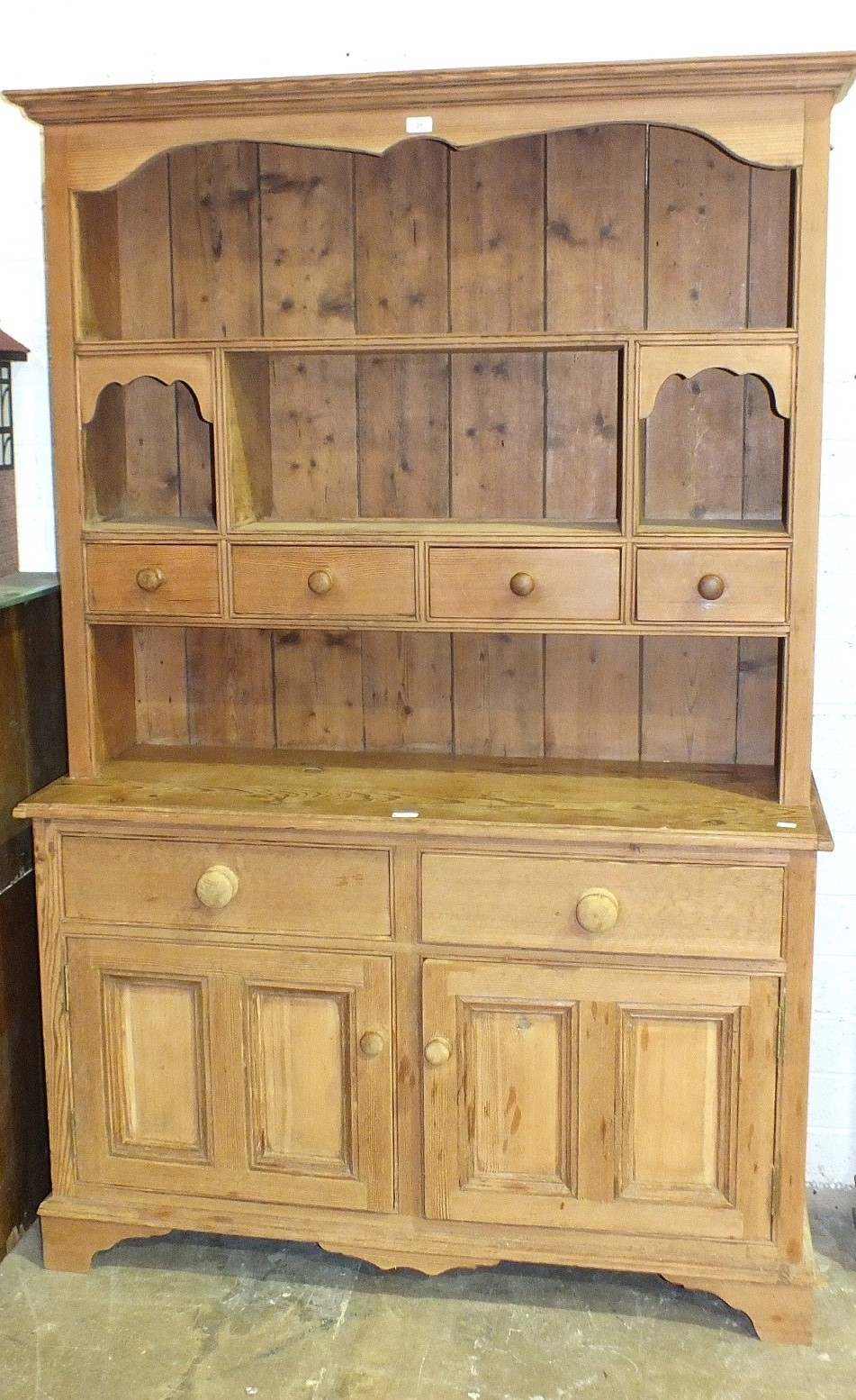 Lot 25 - A stripped pine dresser, the open shelved back fitted with four small drawers, above two frieze