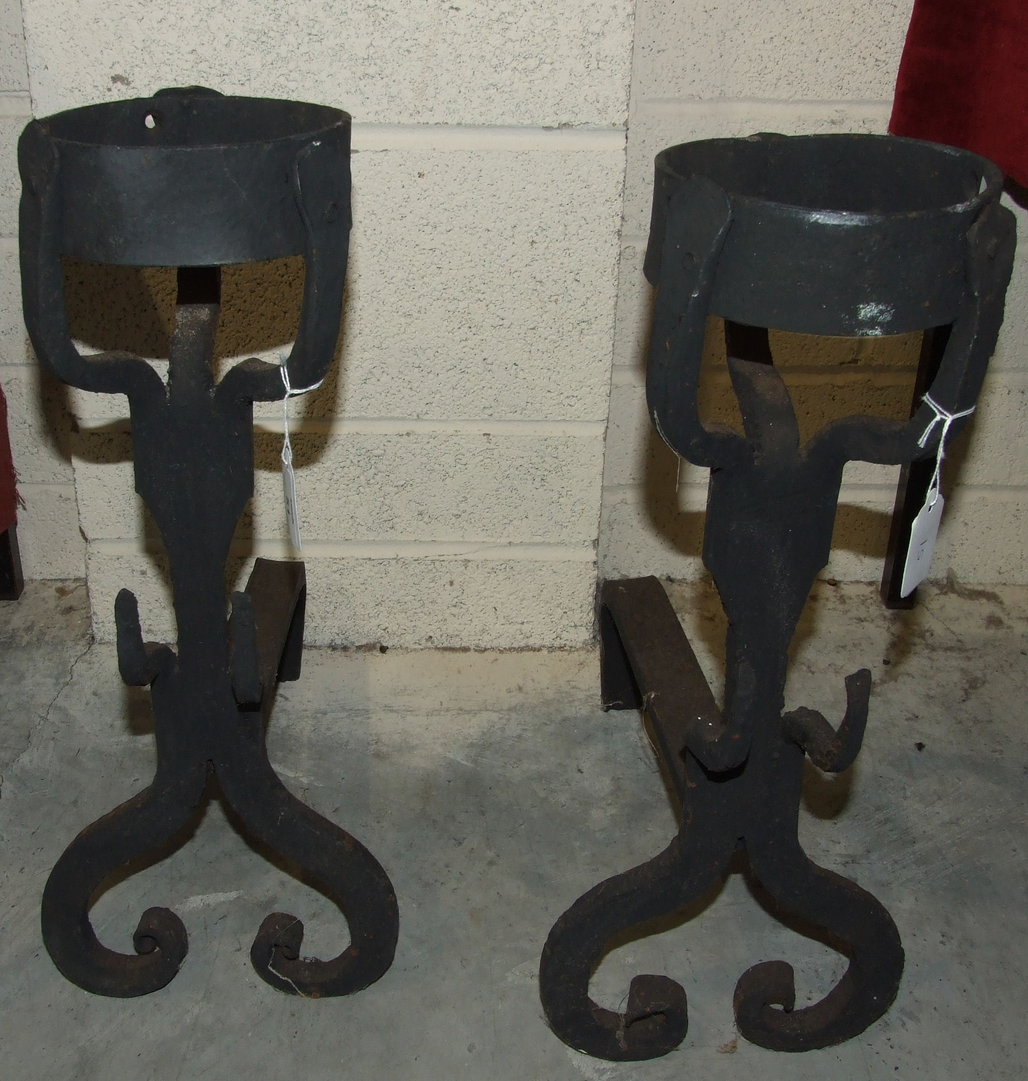Lot 51 - A pair of wrought metal andirons, each with a cresset above scroll supports, 52cm high, (2).