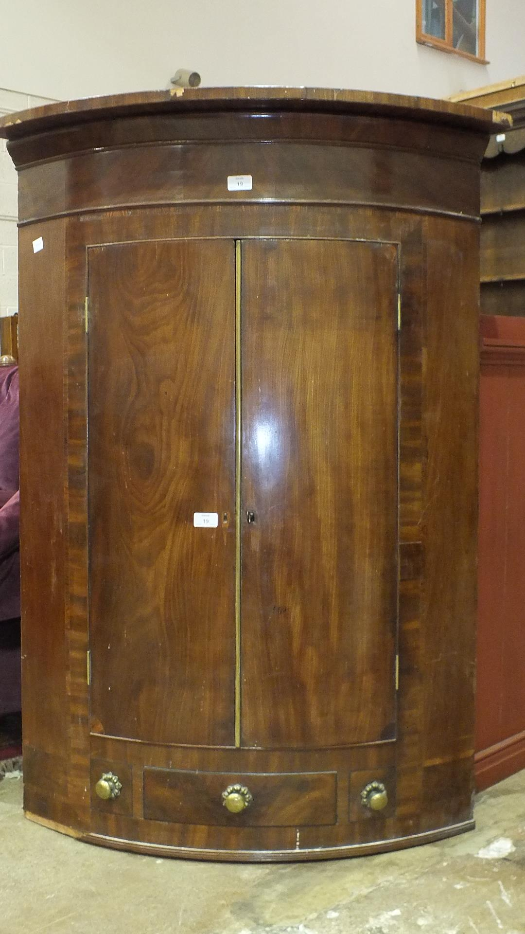 Lot 19 - A Georgian mahogany bow-front corner cupboard.
