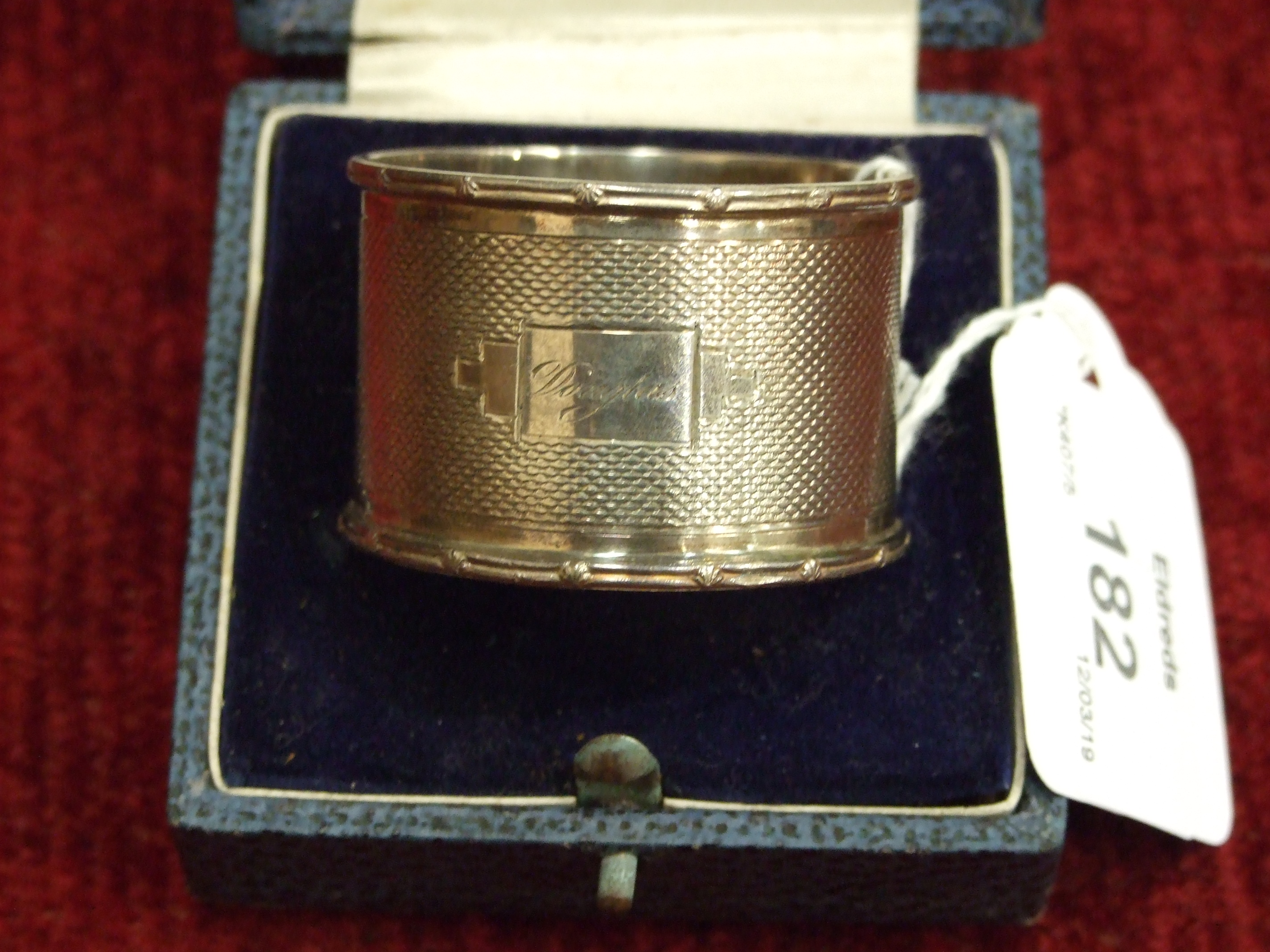Lot 182 - A cased engine-turned silver napkin ring, Birmingham 1941, ___1.3oz, (named) and an Asian white