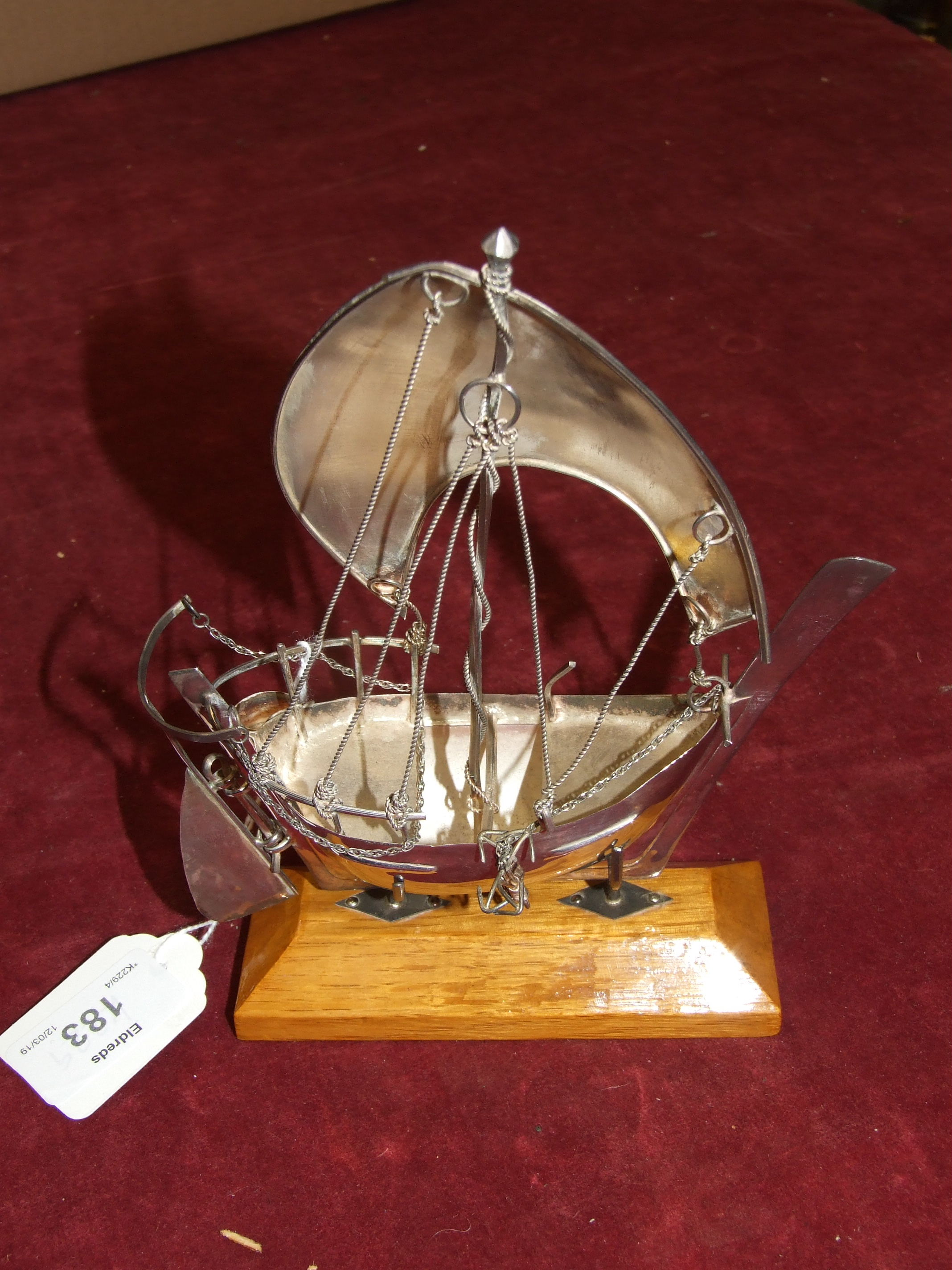 Lot 183 - A white metal model of a dhow, on wood stand, 18cm high, in fitted box.