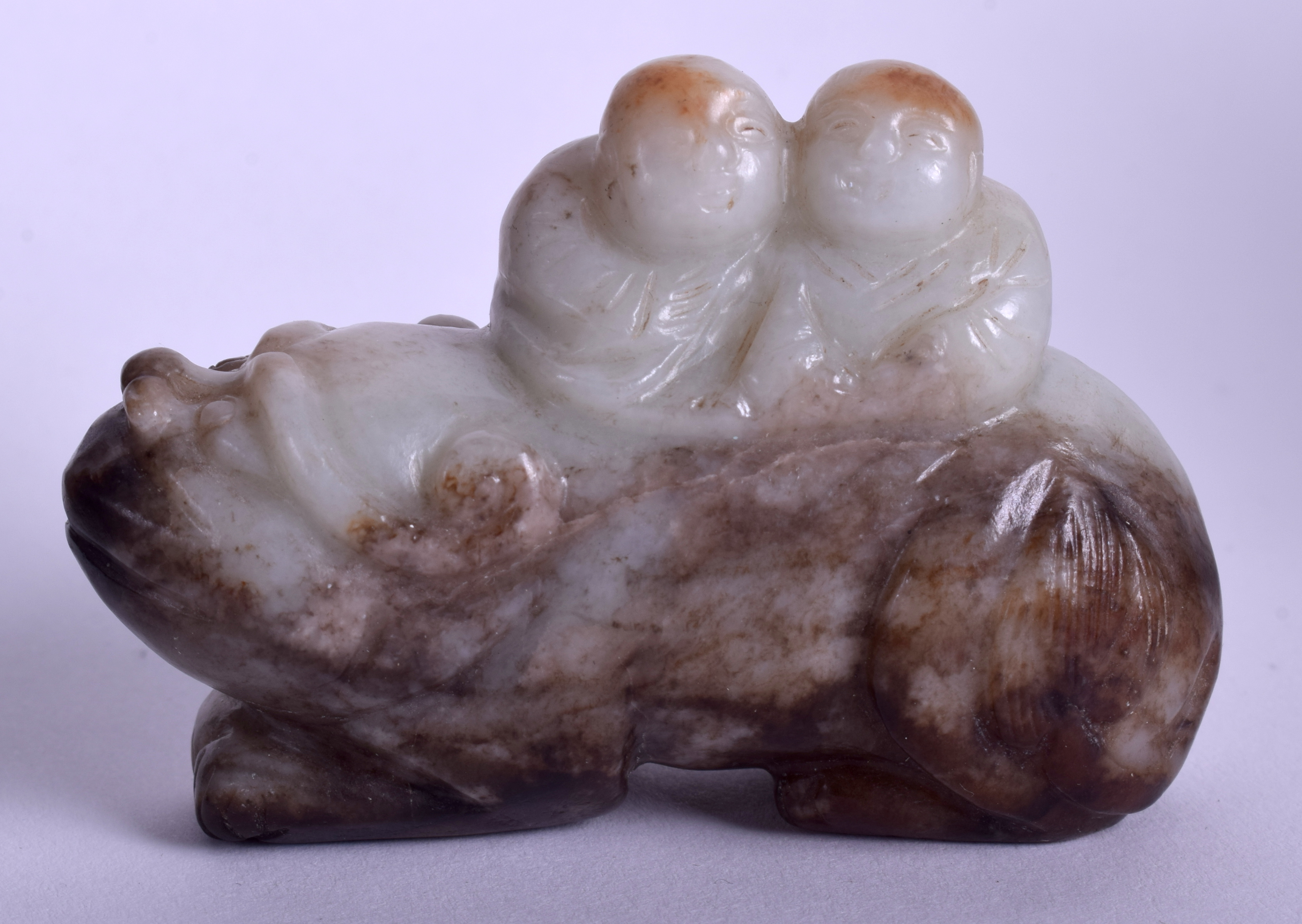 Lot 1594 - A 19TH CENTURY CHINESE CARVED MUTTON GREEN JADE BEAST modelled with two attendants on board. 6.5 cm