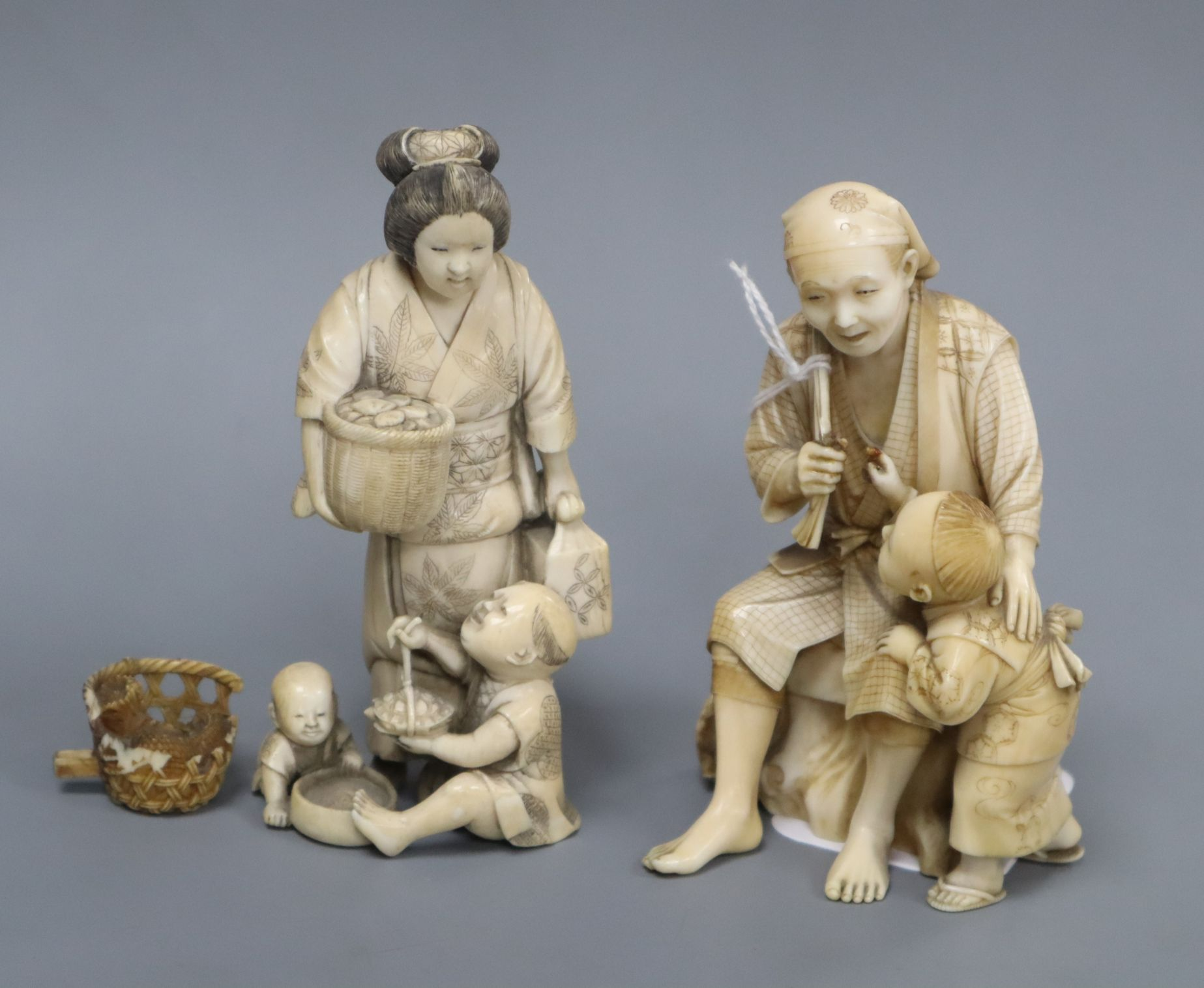 Lot 304 - Two Japanese ivory okimono of figures with children, one signed to a red lacquer tablet, Meiji