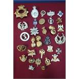 Box containing a quantity of various military cap badges, mostly staybright, for various regiments