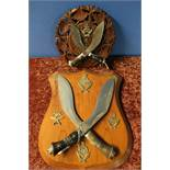Carved wood wall plaque mounted with two Kukri type knives with a crowned Staffordshire Gurkha