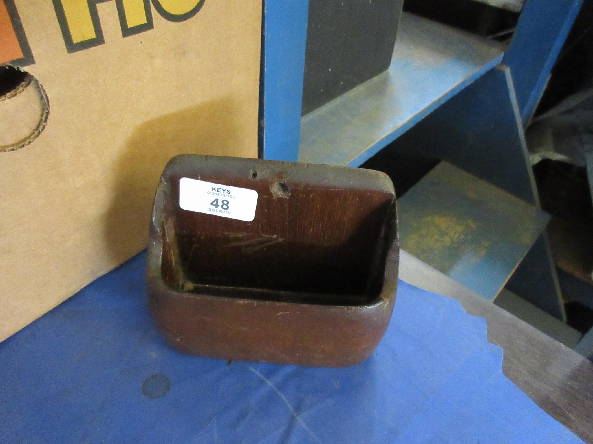 A carved wooden letter holder or candle pocket