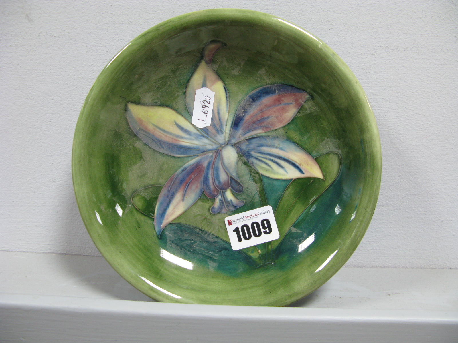 "Lot 1009 - A Moorcroft Pottery Dish, of shallow circular form, painted in the ""Orchid"" pattern in pink, blue"