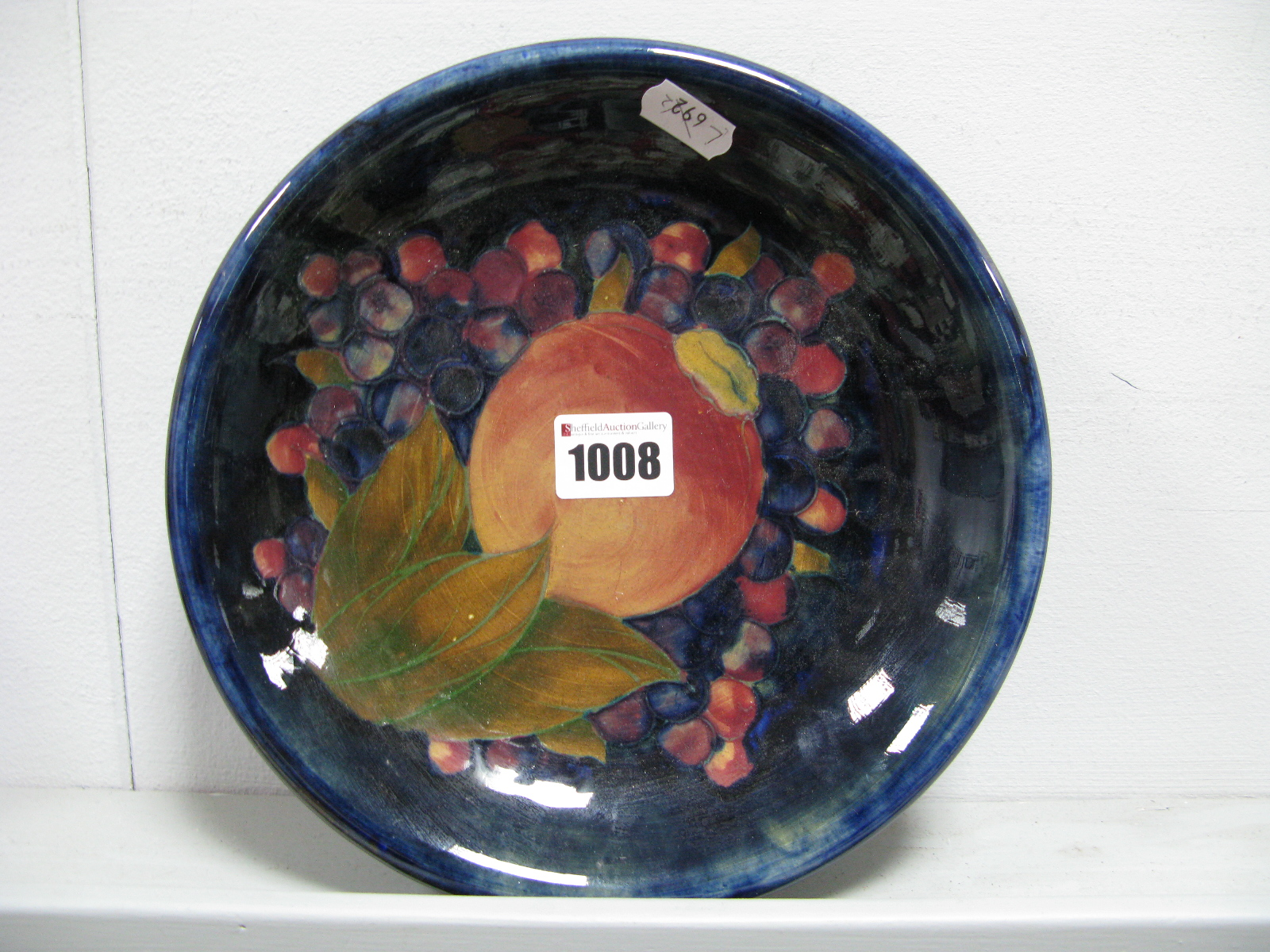 "Lot 1008 - A Moorcroft Pottery Dish, of shallow circular form, painted in the ""Pomegranate"" pattern against"