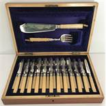 An Edwardian wooden cased cutlery set of fish and fruit knives & forks with servers.