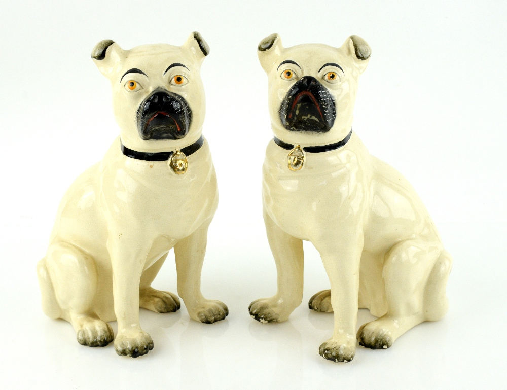 Lot 3006 - A pair of 19th century Staffordshire models of pugs, 27 cm high.