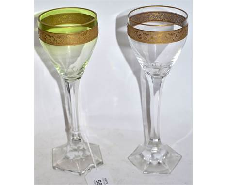 Pair of wine glasses, probably Moser, with green tint and a gilt engraved band above a faceted stem and hexagonal shaped foot