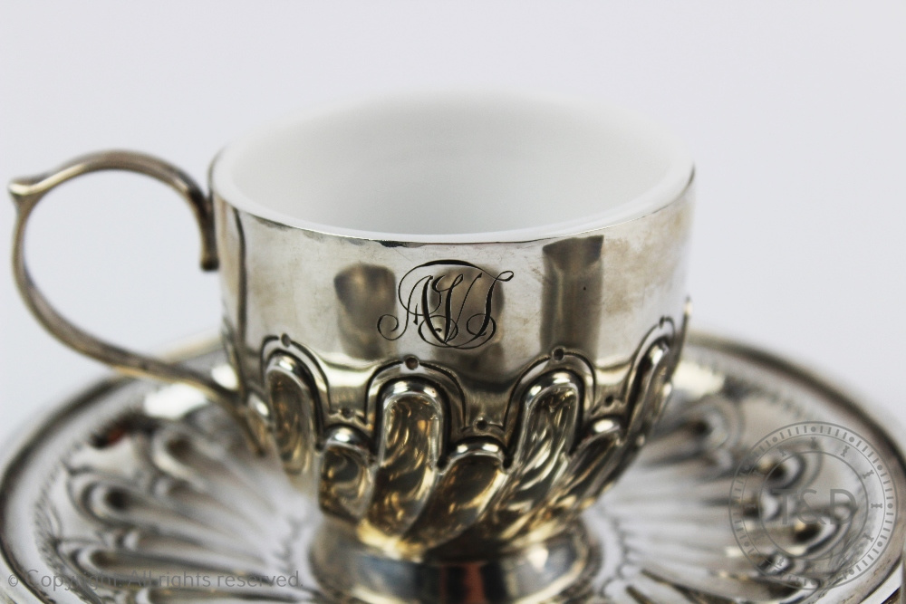 Lot 29 - A Victorian silver tea cup and saucer, London 1896, the cup with milk glass liner,