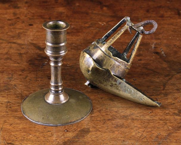 Lot 36 - An Early Patinated Copper Alloy Candlestick with a flanged socket and reel stem peaned to a