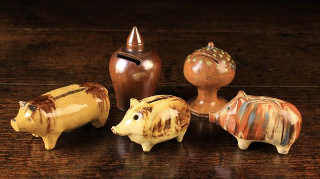Lot 54 - A Group of Five Pottery Money Boxes: A globular box with nipple finial and a raised pedestal base