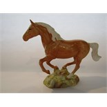 A Beswick model of a galloping palomino pony with impressed number to base 1374